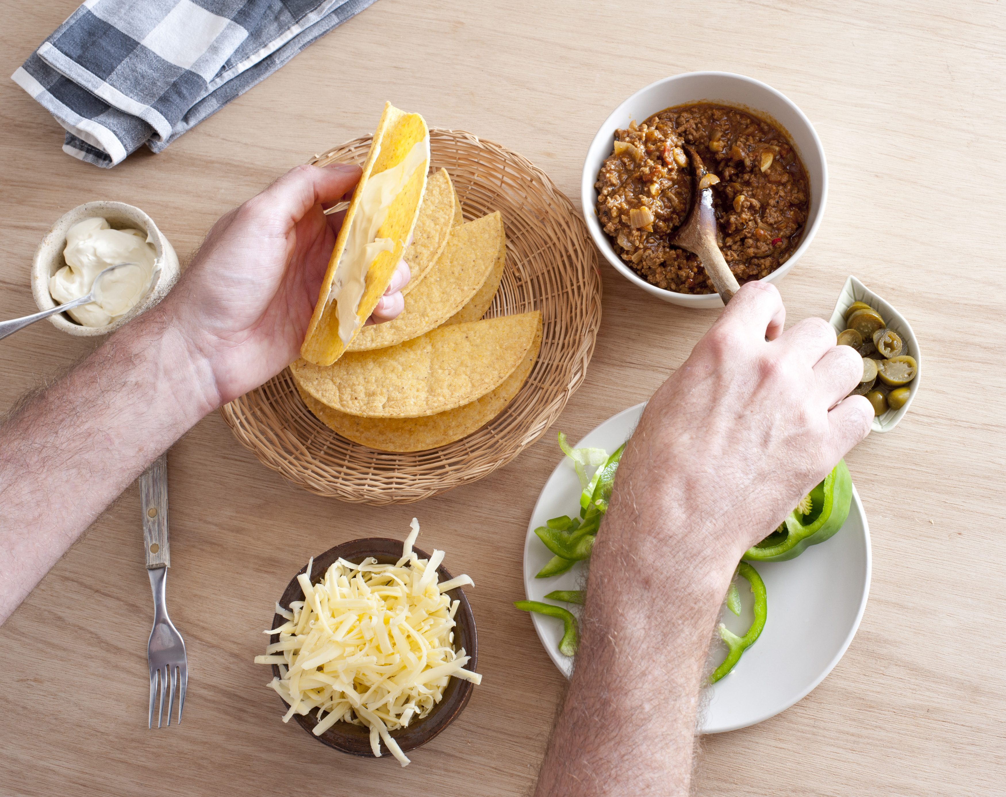 Overhead view of the hands of a man fixing himself a taco with fresh ingredients spooning them in from individual bowls on a table
