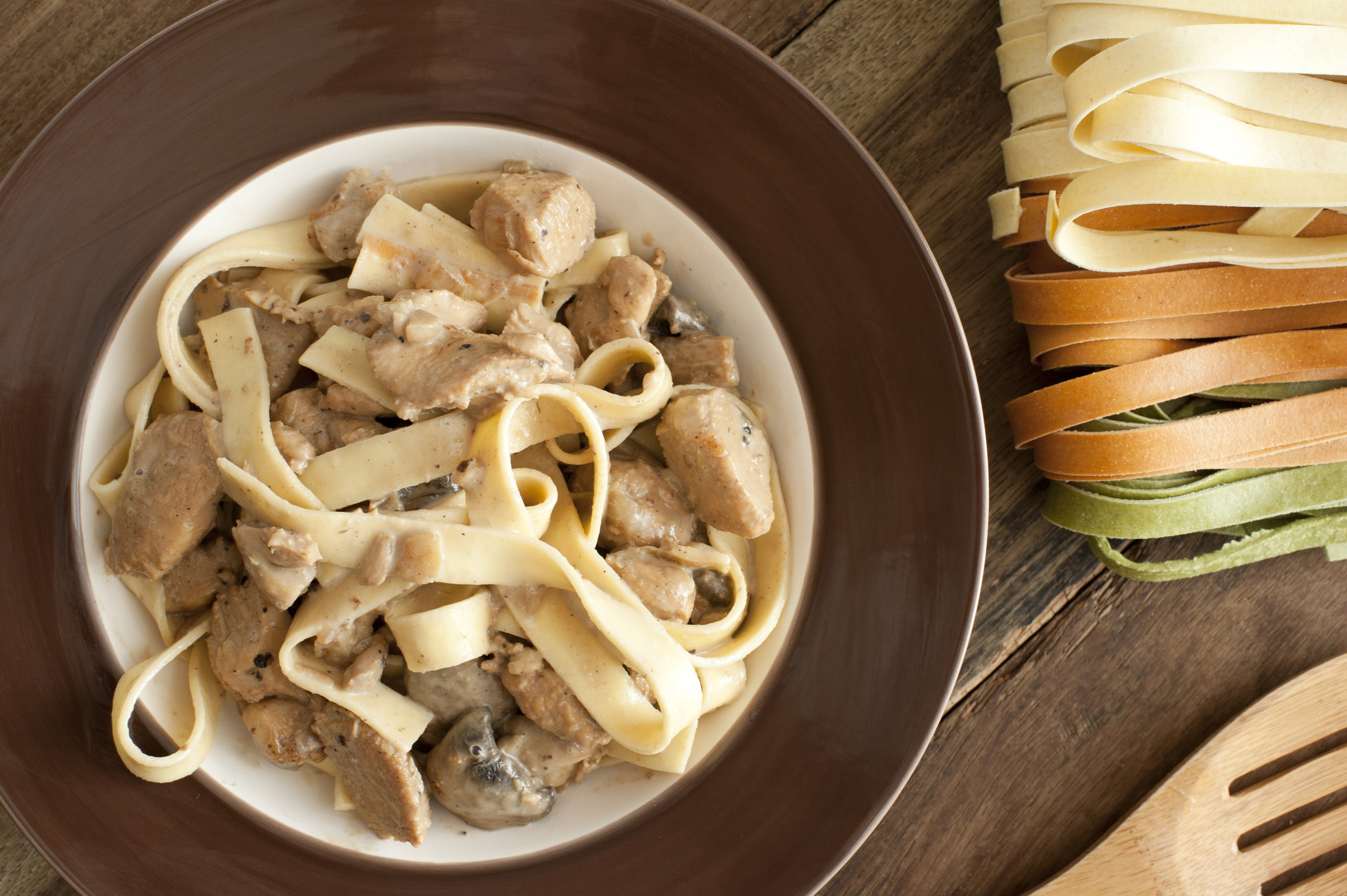 First person view on warm and delicious bowl of chicken, mushrooms and tagliolini in bowl with pasta on table