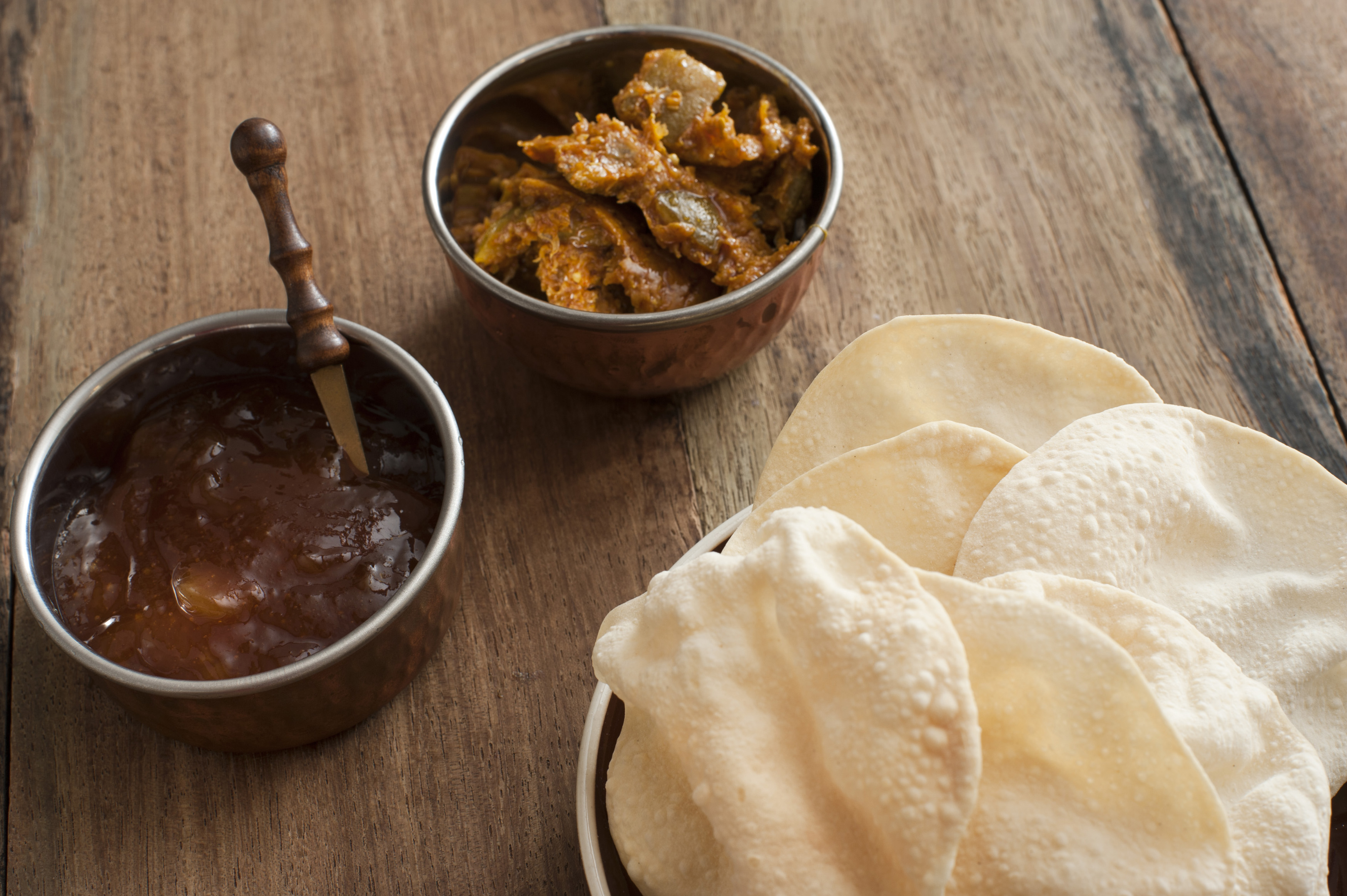 Side dishes for an Indian curry with crispy papadums , chutney and spicy roasted vegetables on a wooden table