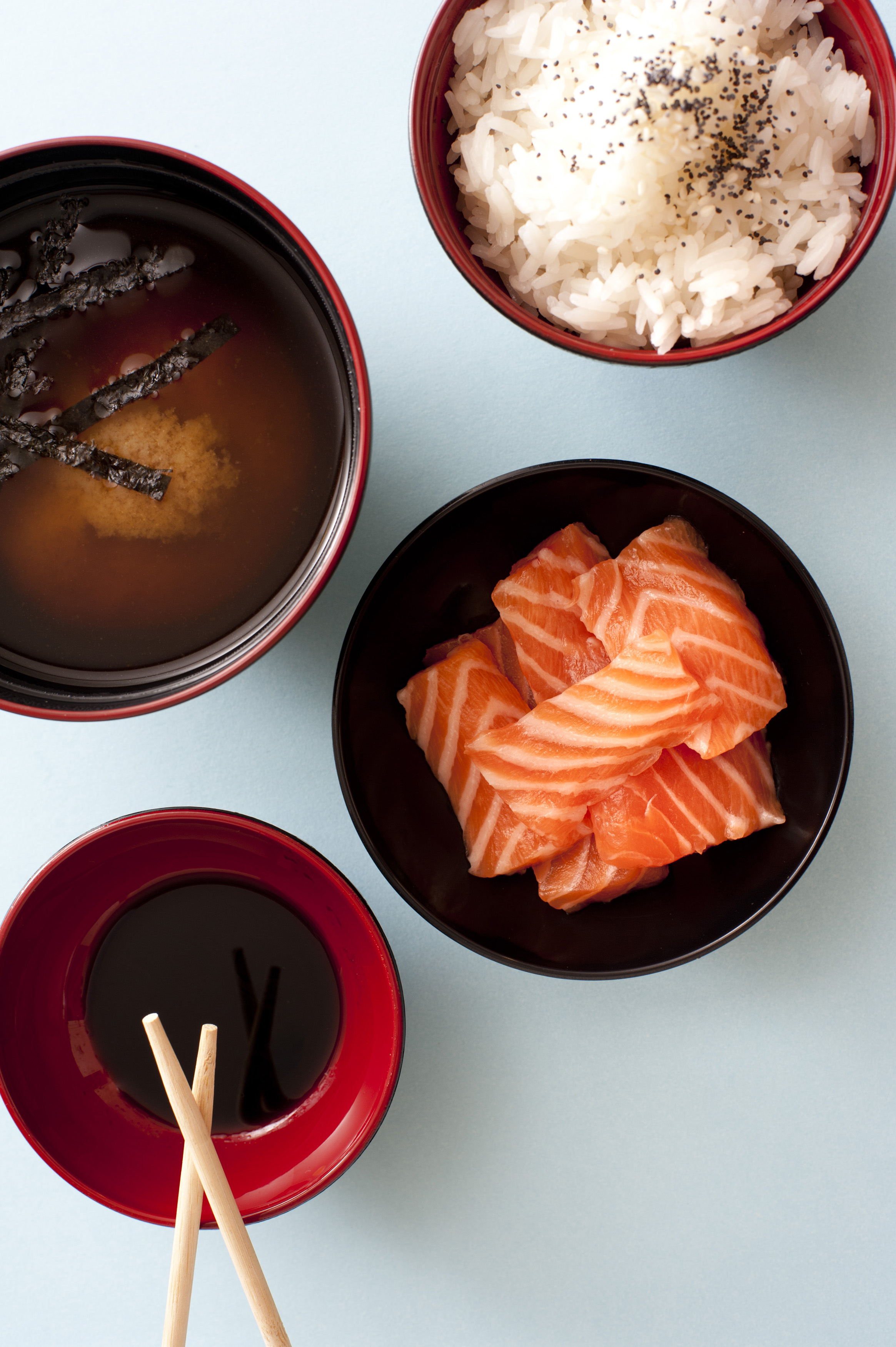 Traditional Asian sashimi with raw salmon with rice, miso and soy sauce in individual bowls , overhead view