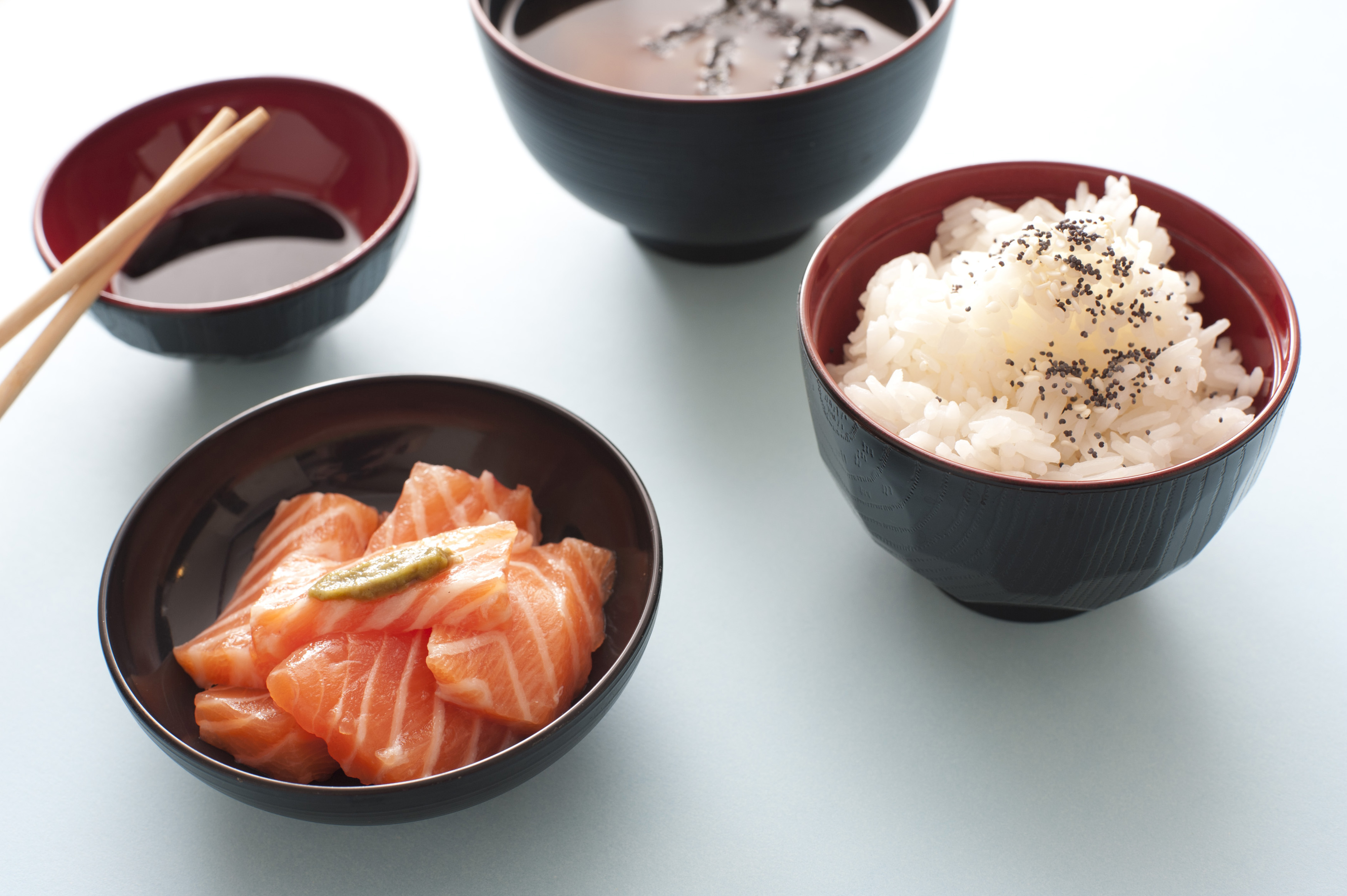 High Angle Culinary Still Life View of Asian Sushi Meal Consisting of Raw Salmon, Rice, Miso Soup and Soy Sauce Served in Bowls with Chopsticks