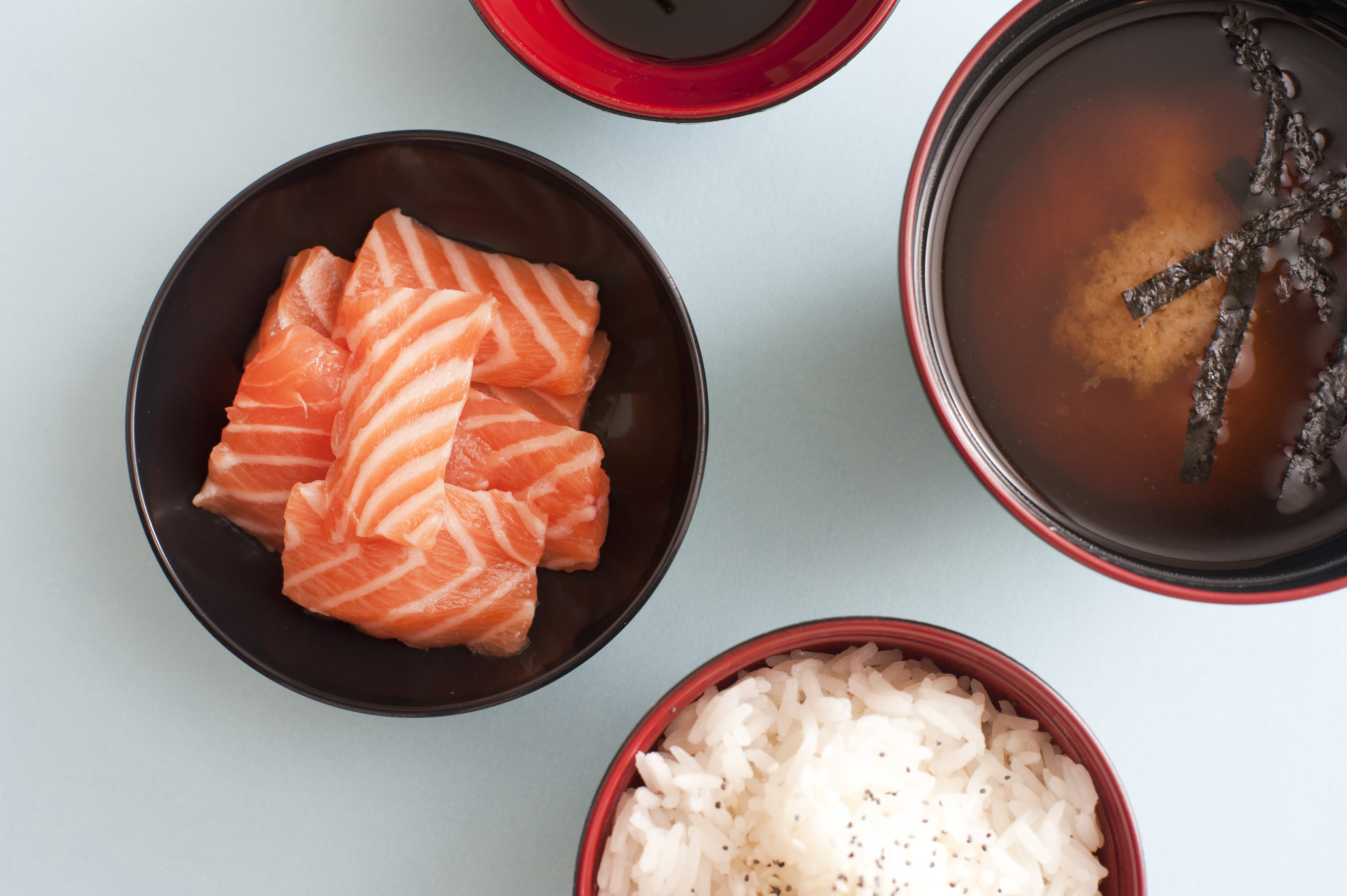 japanese bolws of salmon sashimi, miso soup and rice on a blue background