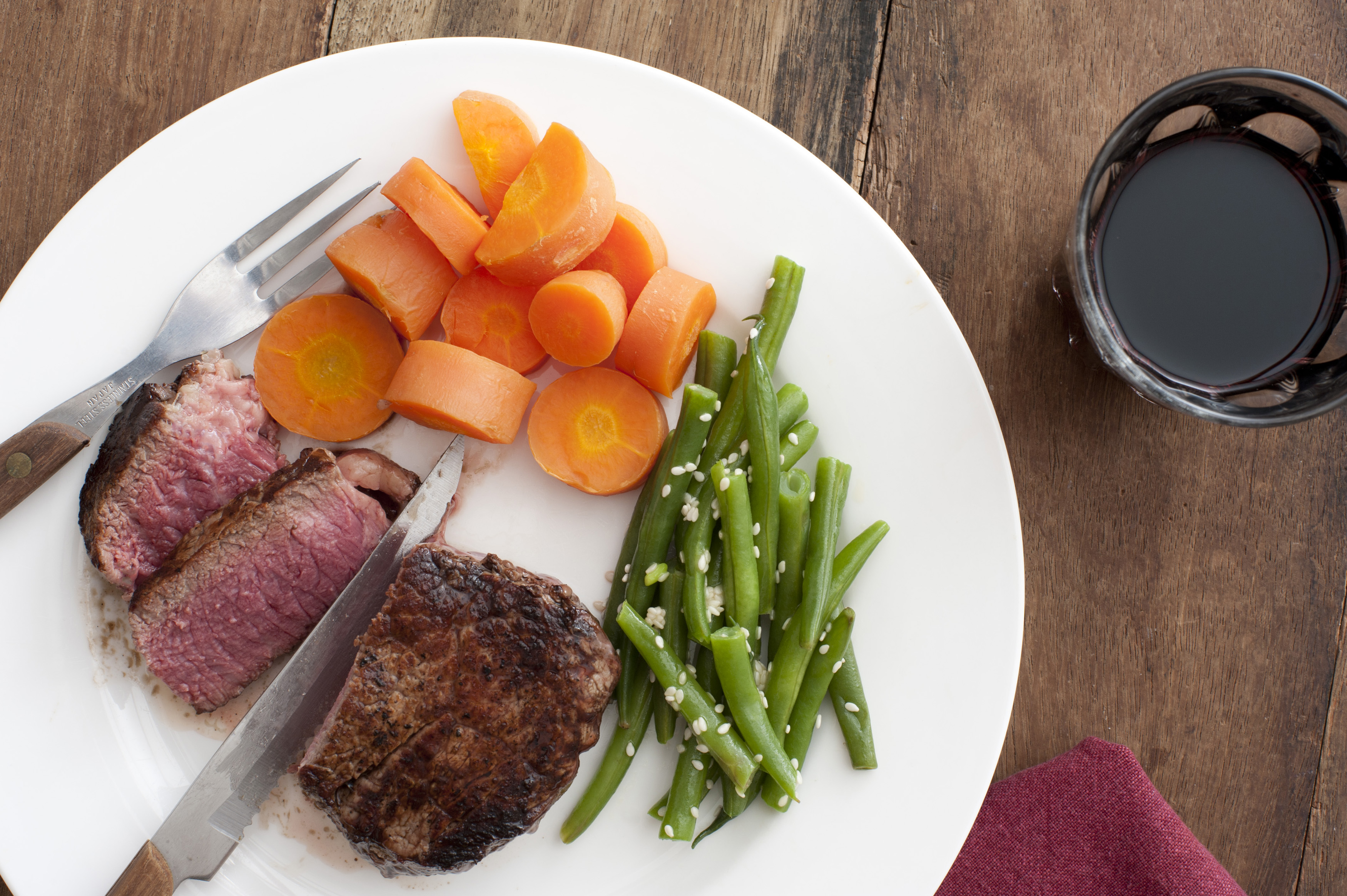 Serving of tasty medium rare fillet steak cut through to show the tender meat with fresh green beans and carrots, overhead view with a glass of red wine