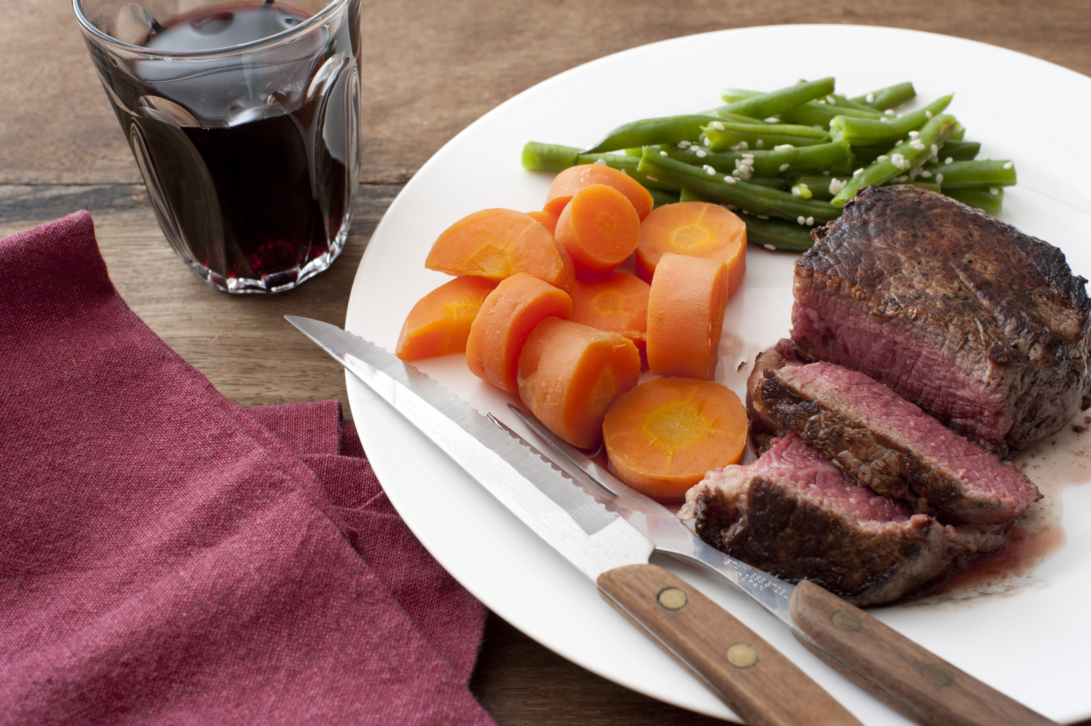High Angle Still Life of Healthy Hearty Meal of Roast Beef, Diced Carrots and Green Beans Served on White Plate with Fork and Knife, on Wood Table with Beverage and Cloth Napkin