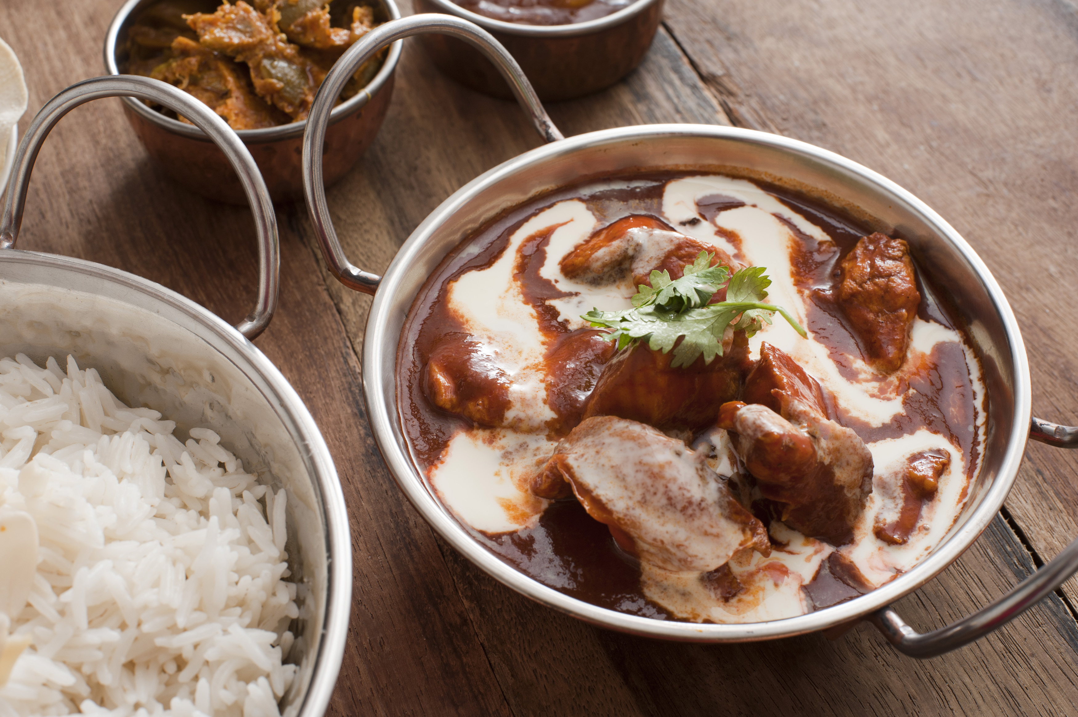 Delicious creamy sauce on cooked chicken with white rice and appetizers in metal serving pots on wooden table