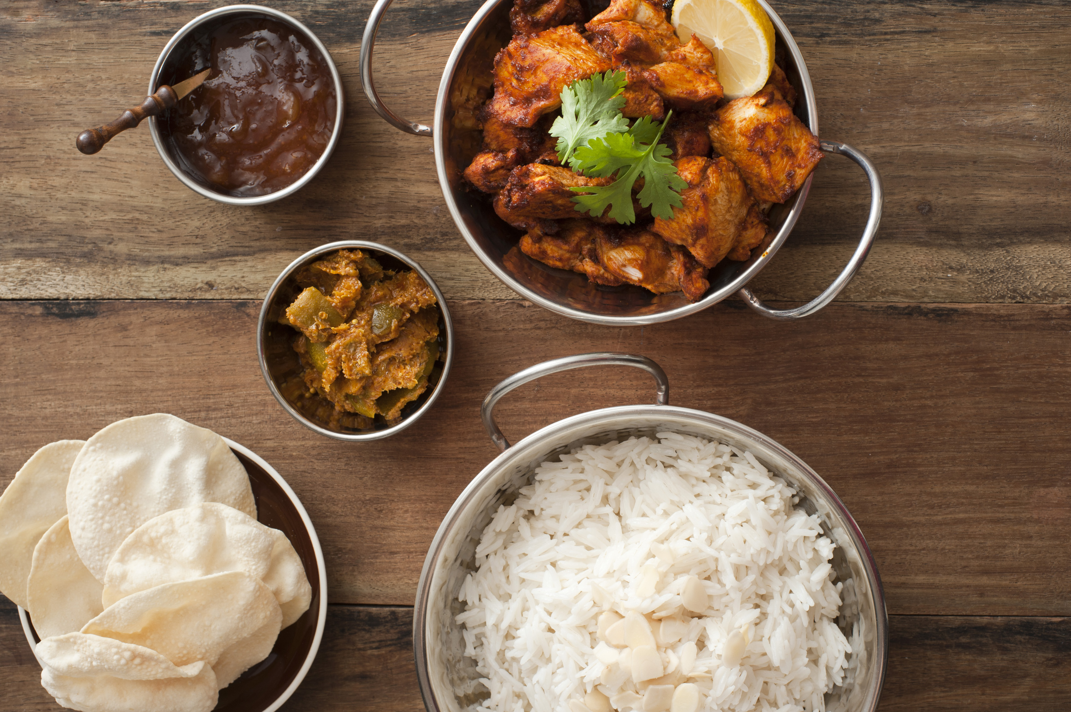 Overhead view of tandoori chicken and chutney beside other exotic food in pots on wood table