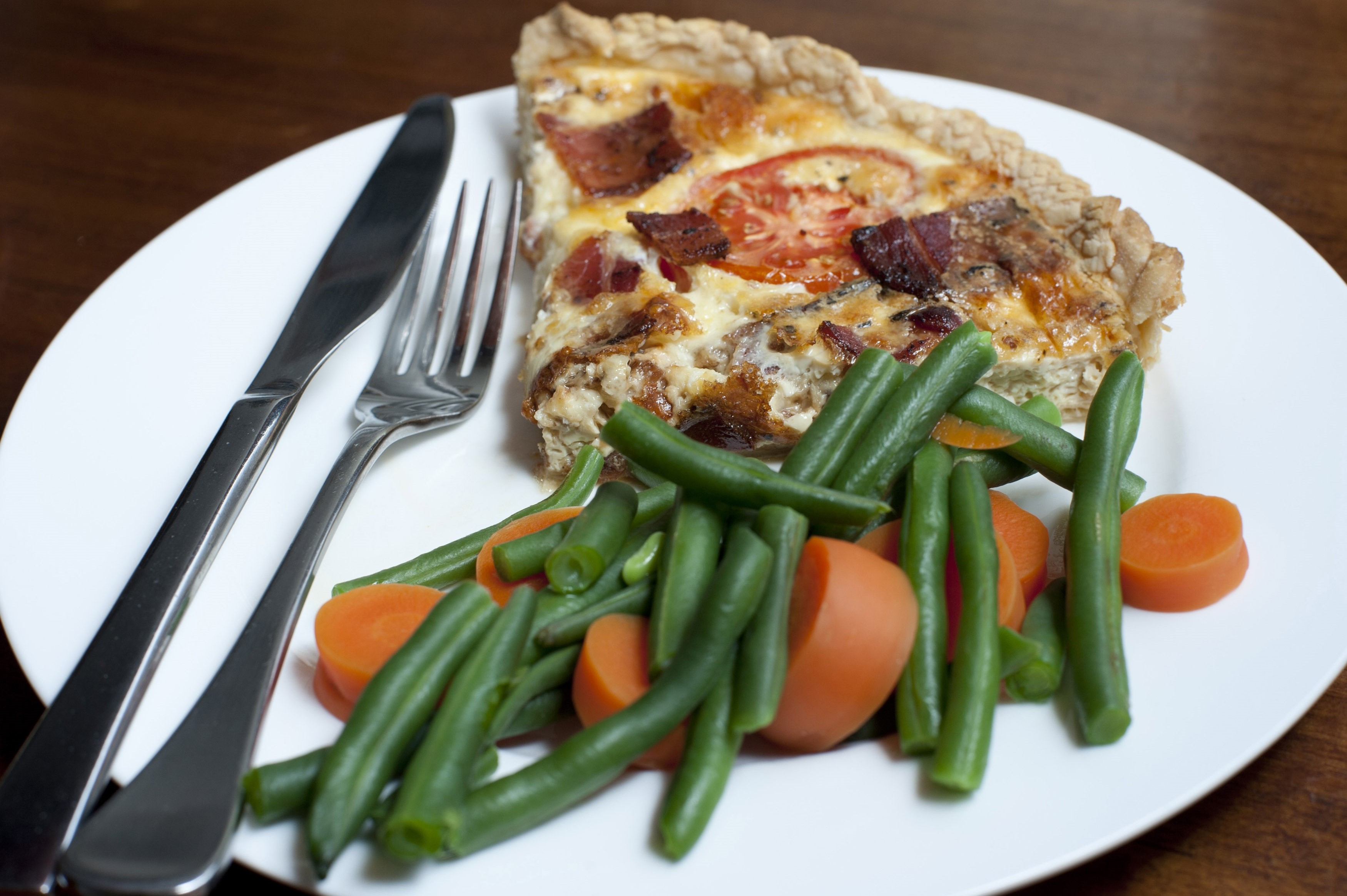 Slice of savoury quiche with fresh cooked carrots and green beans served on a white plate with cutlery over a black background