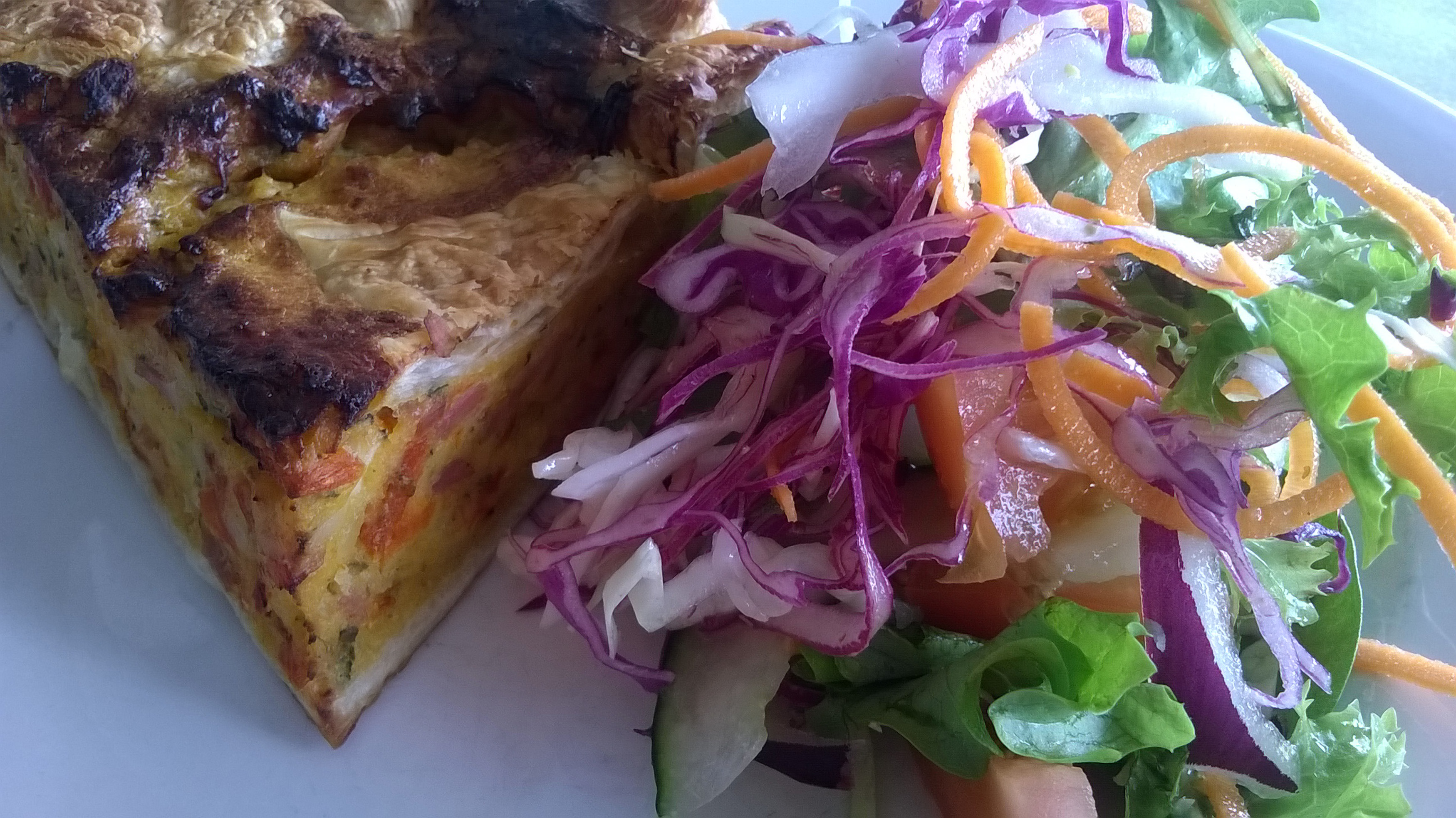 Close up on slice of baked quiche beside red cabbage, onion, lettuce and carrot salad