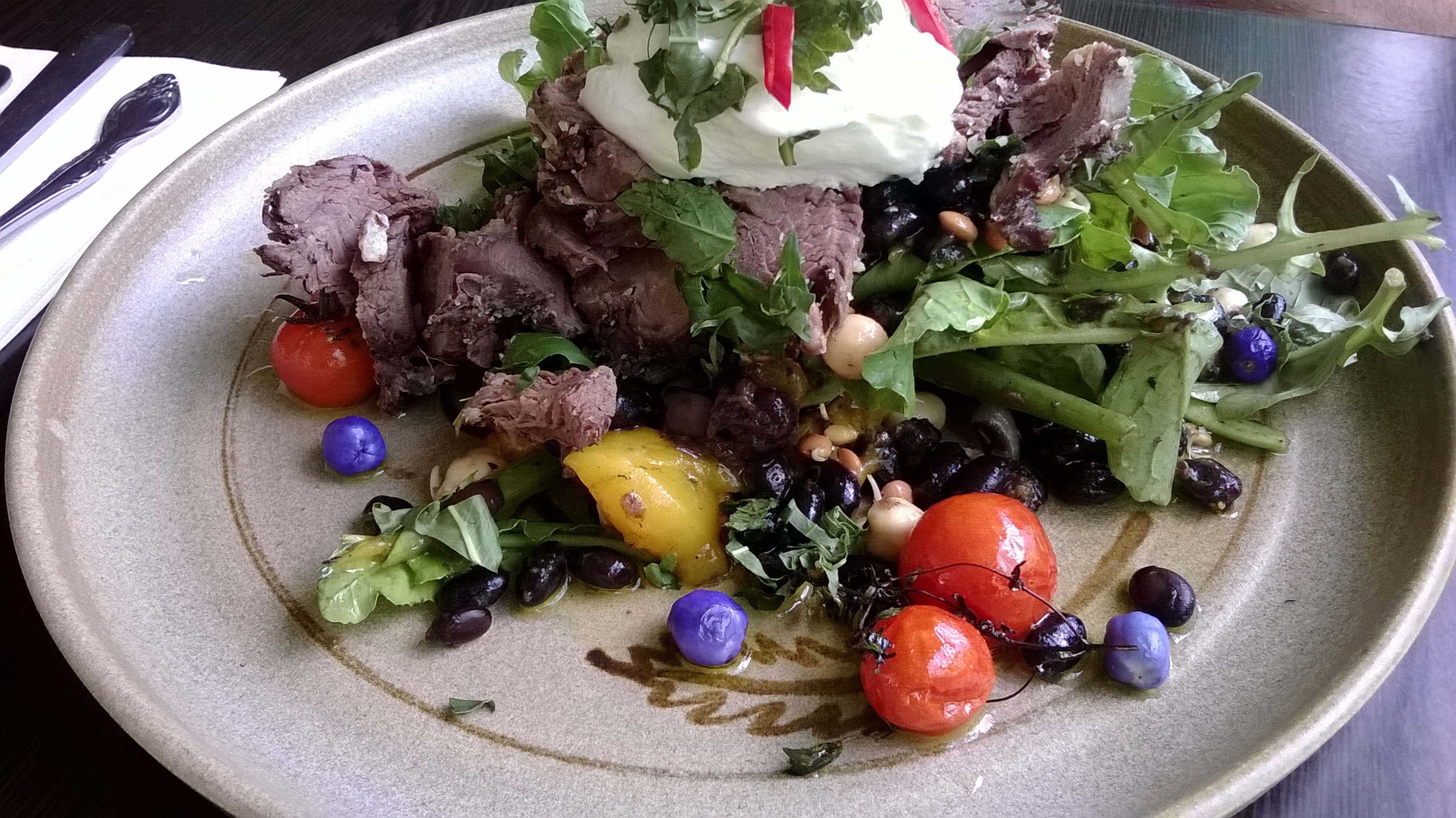Beautiful plate of delicious rustic beef salad with black beans, greens, cherry tomatoes and a dollop of sour cream topped with fresh herbs