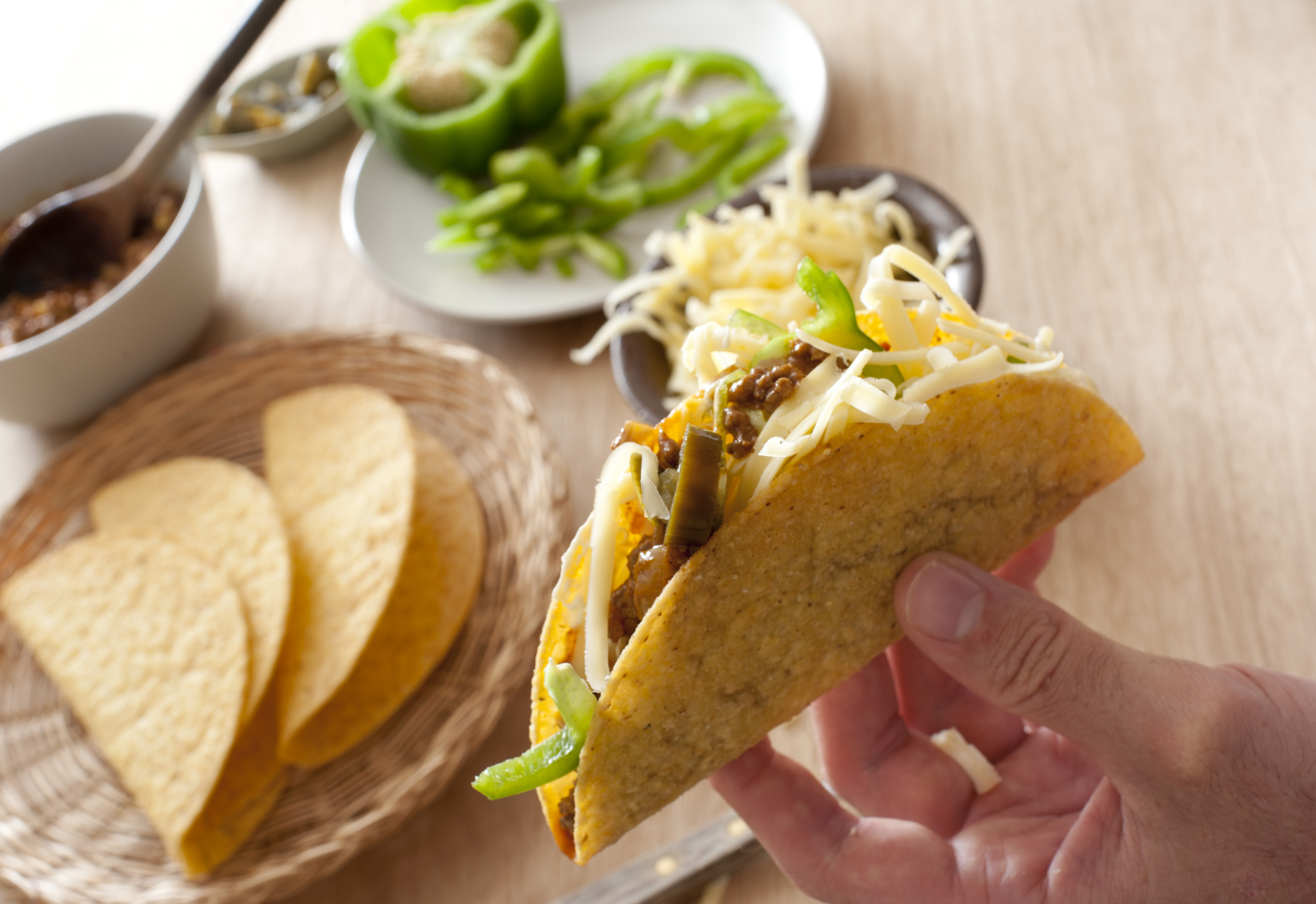 Man preparing a ground beef taco adding fresh green peppers and grated cheese for a tasty lunchtime snack