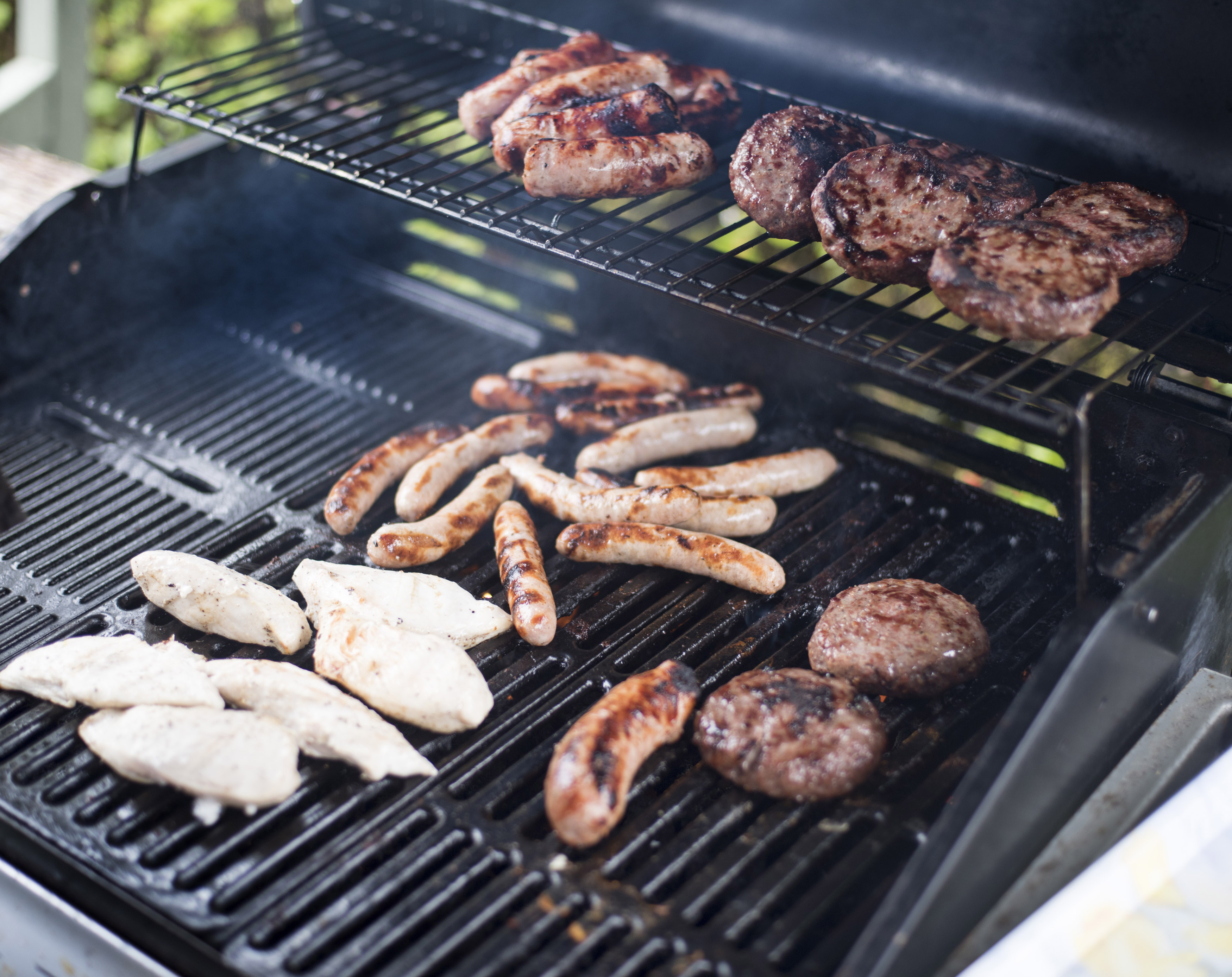 Assorted meat grilling over a BBQ fire with chicken breasts, sausages and beef patties