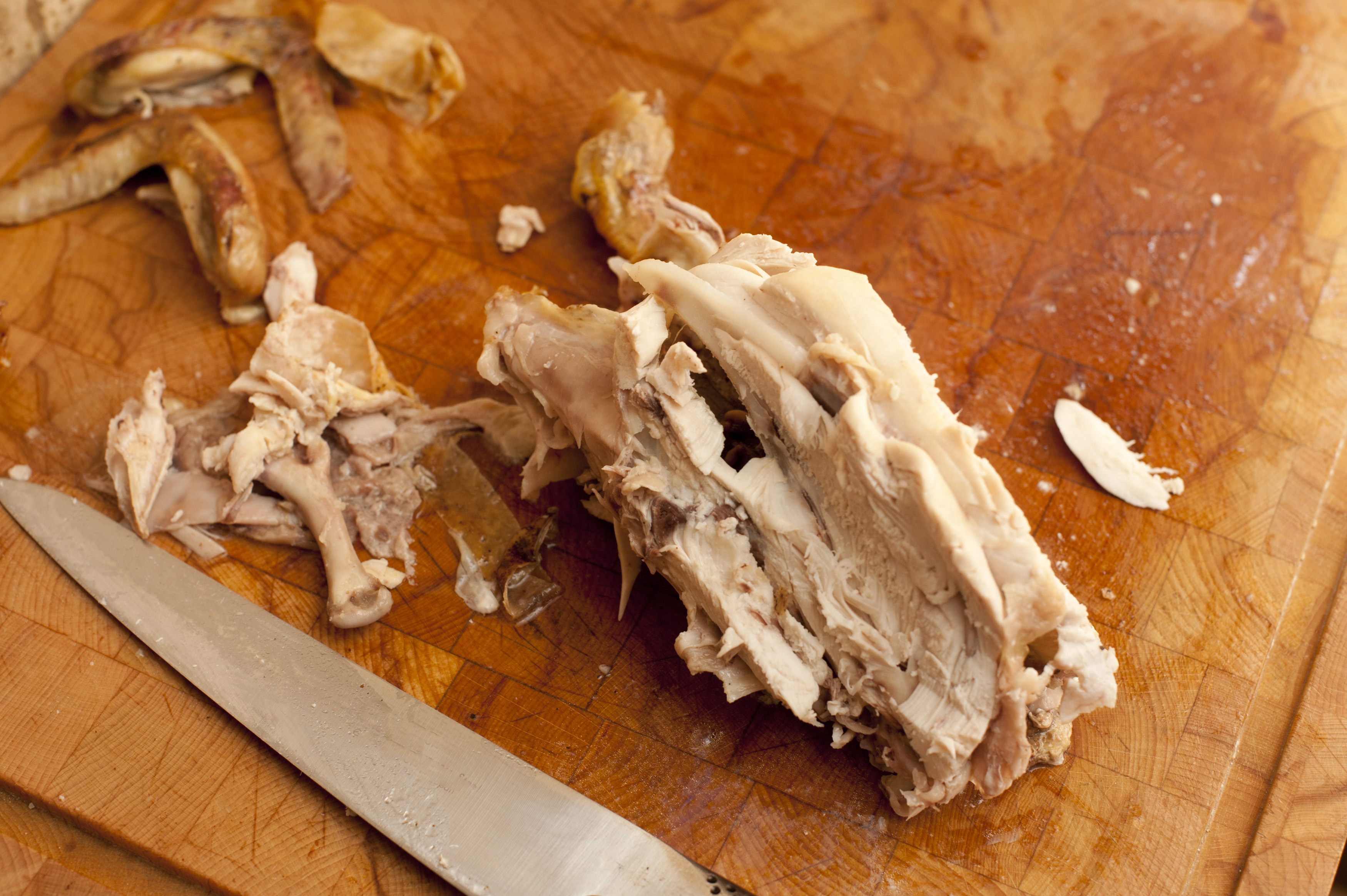 The carcass and left over remnants of a roast chicken on a wooden board with a carving knife, viewed from above