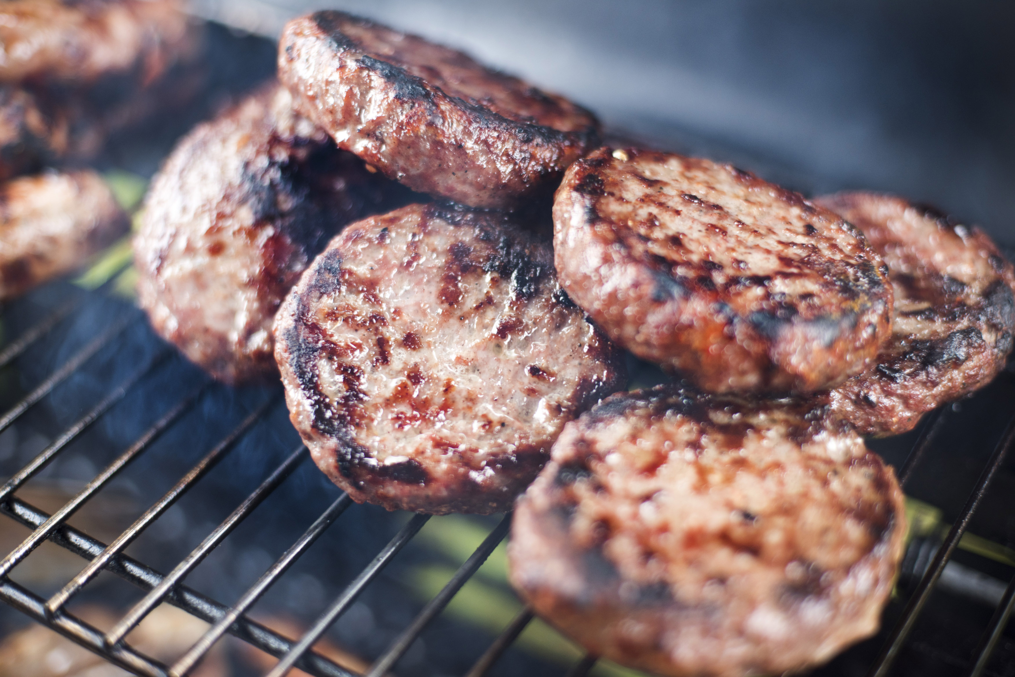 Grilled beef burger patties on a BBQ grid over the hot coals in a close up view