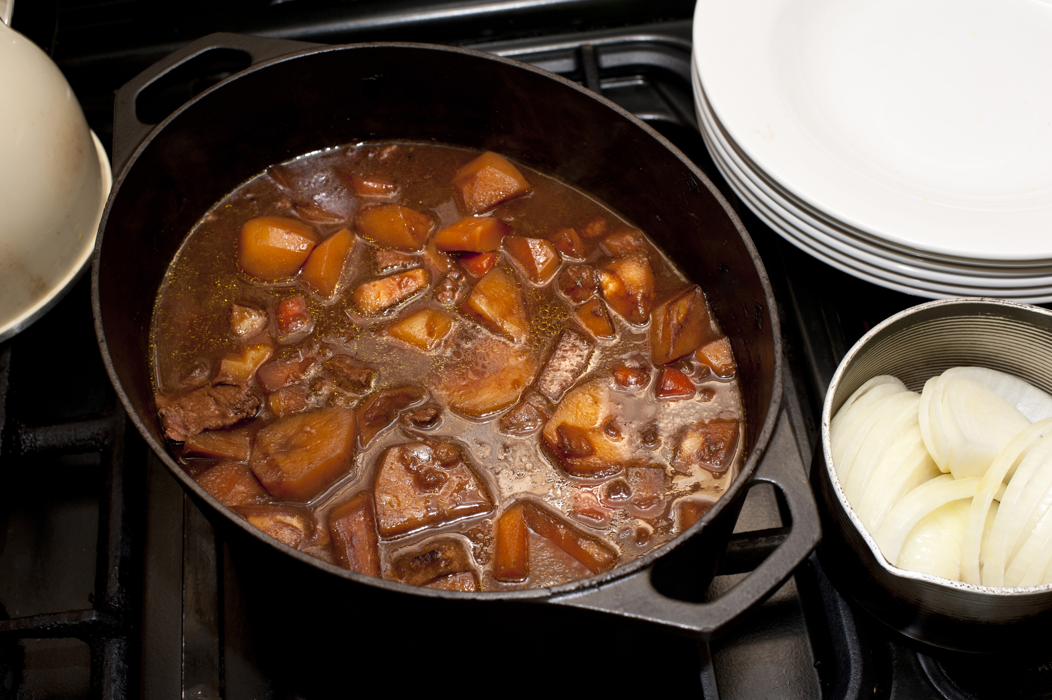 Delicious hot soup with potatoes, meat, different vegetables in saucepan on stove. From above