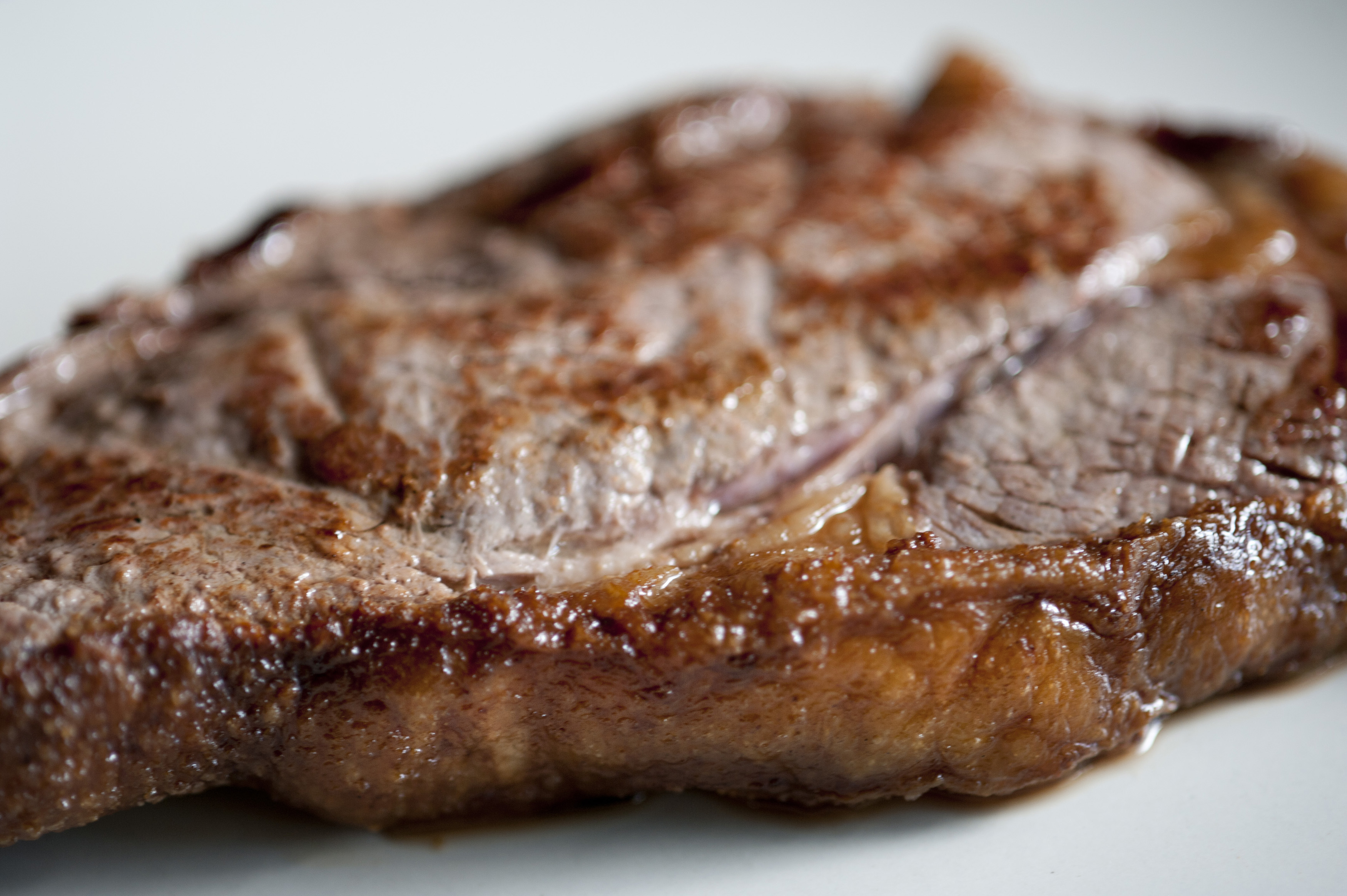 Fatty steak with a close up view of the cooked oily fatty rind on a portion of beef rump steak
