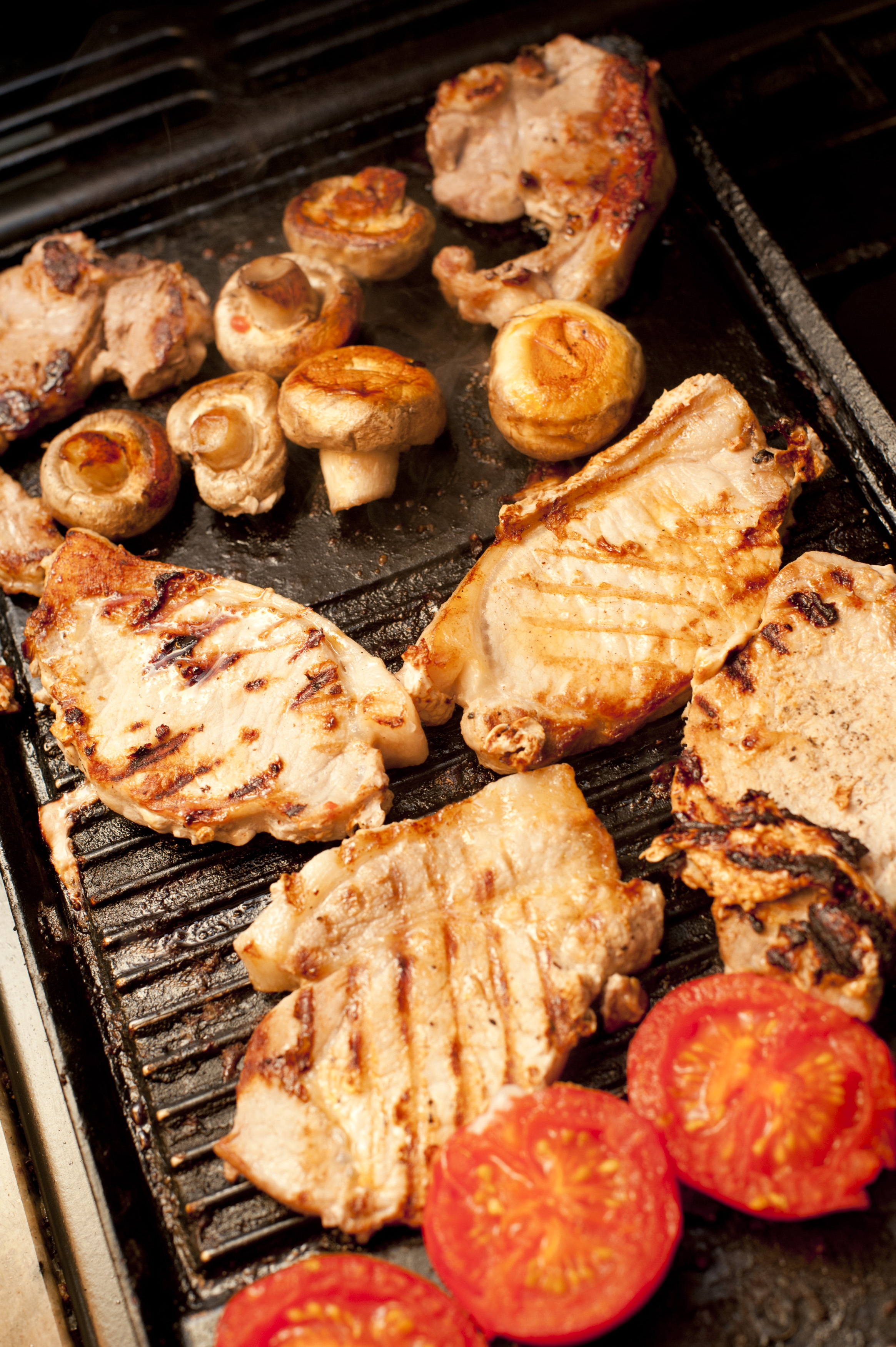 Grilled English breakfast with fresh mushrooms, tomato and pork cutlets cooking on the grill, high angle view