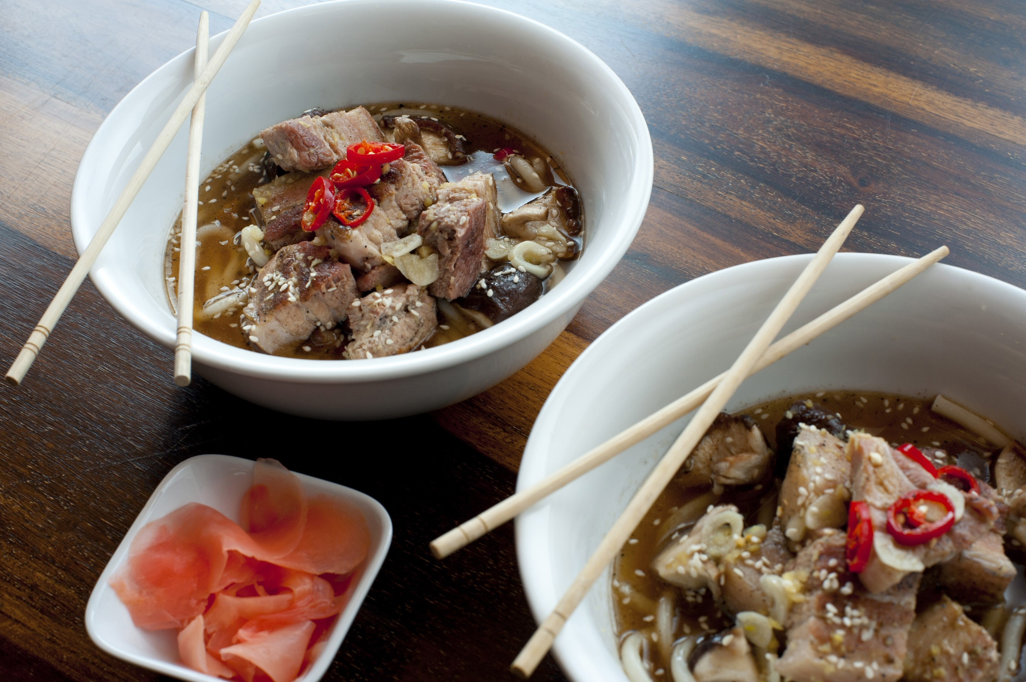 Japanese ramen, or noodles served in a broth garnished with vegetables and meat, served in two bowls with chopsticks