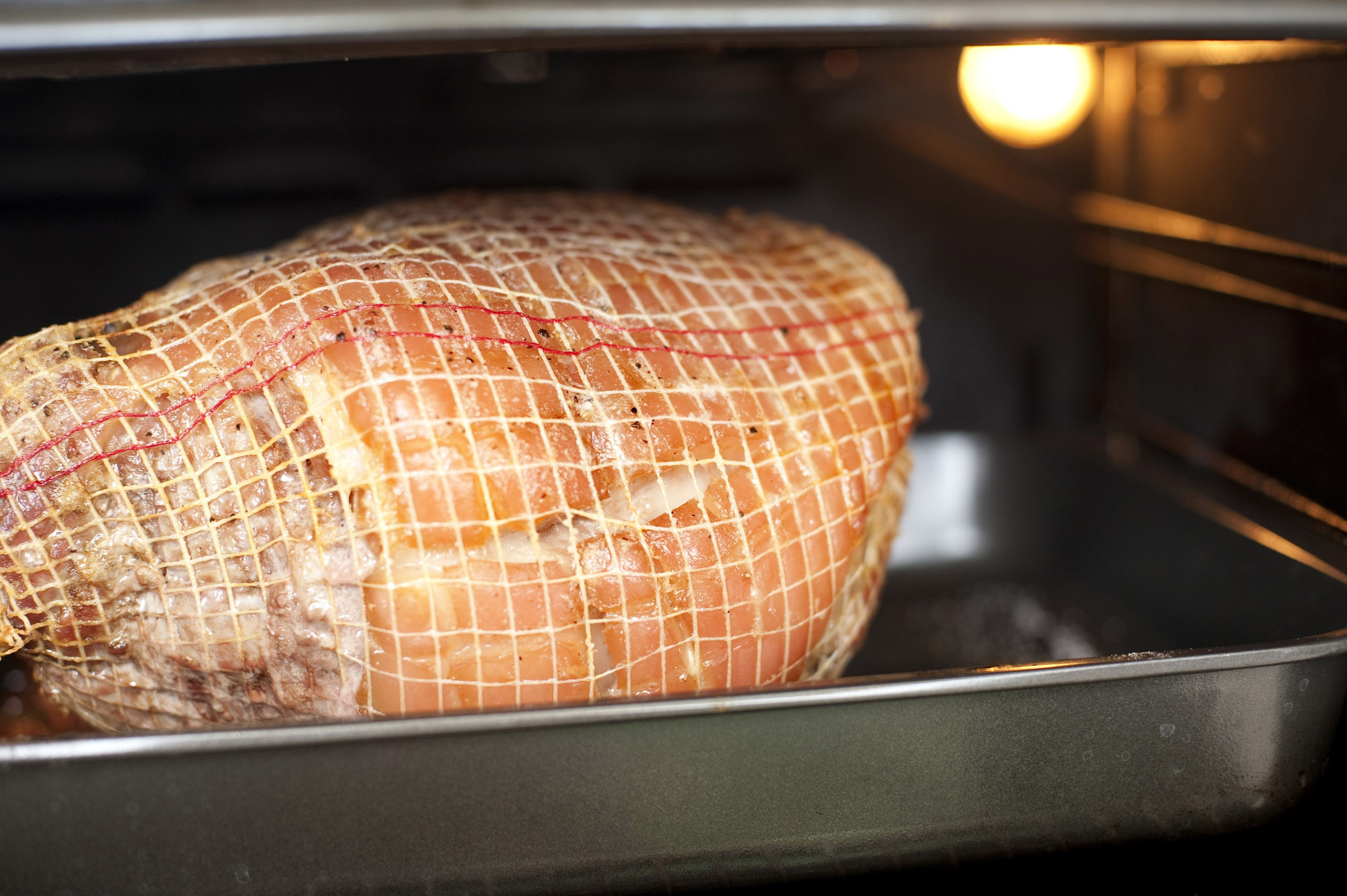Interior view of a cut of pork roasting in the oven bound in net on a grilling pan