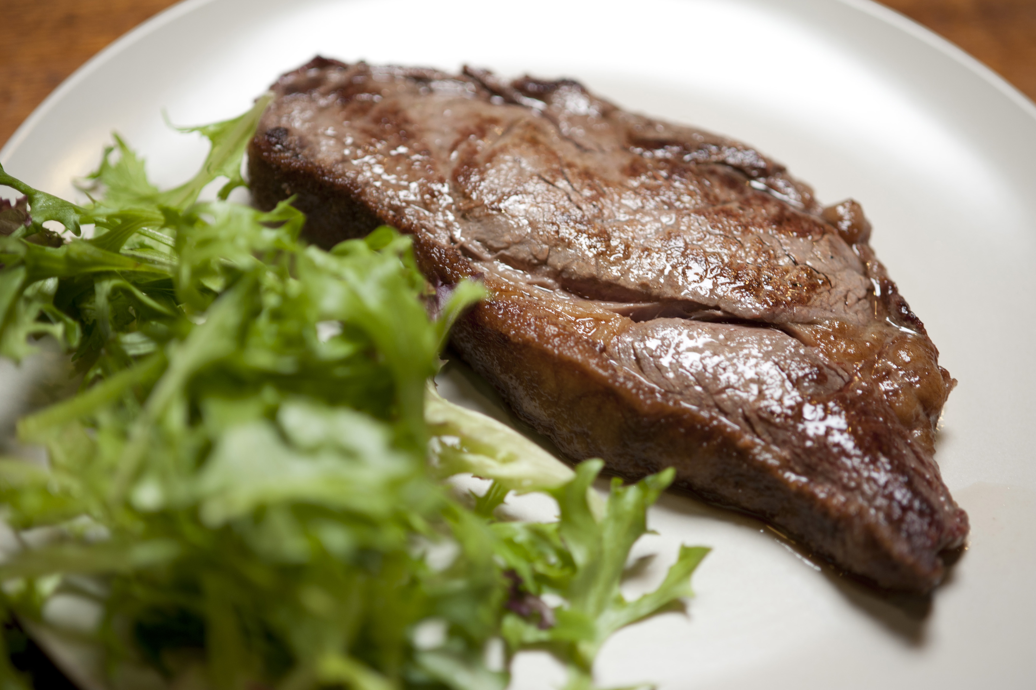 Low angle view of a juicy grilled sirloin steak plated with fresh leafy green salad on a white plate