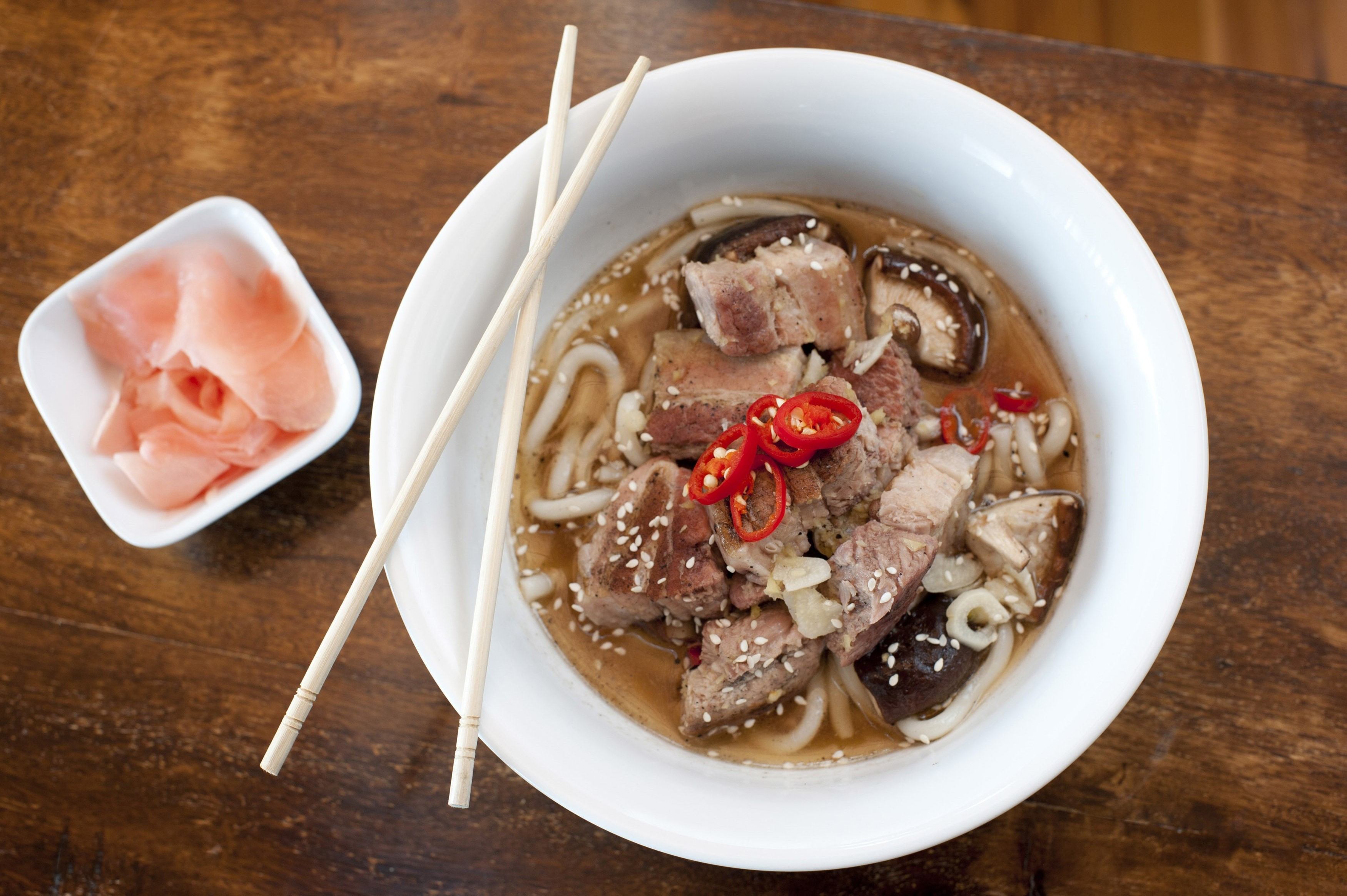 Japanese pork ramen, a broth containing noodles, vegetables and meat, overhead view of a serving in a bowl with chopsticks
