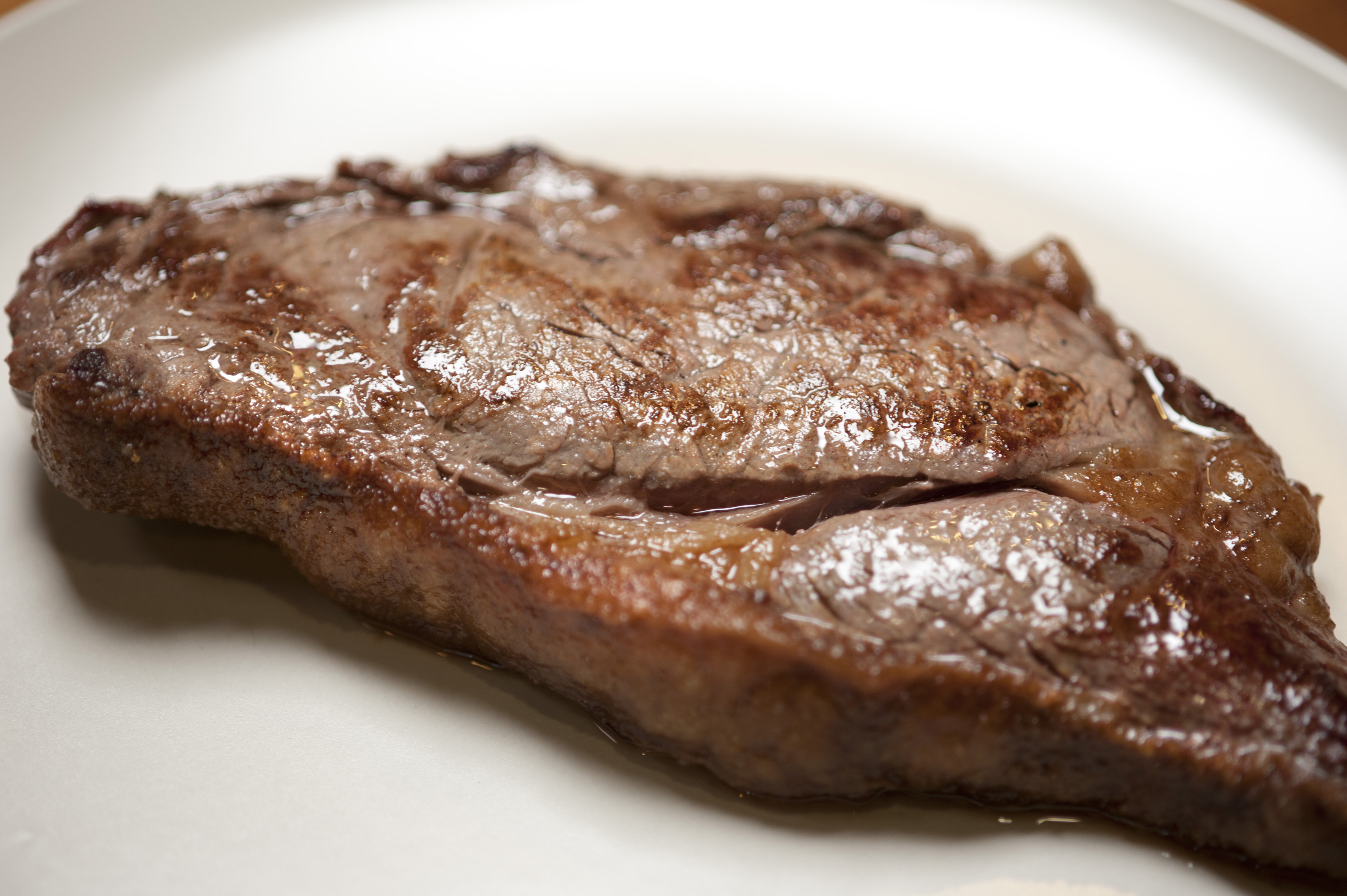 Close up low angle view of a cooked portion of sirloin steak with crispy fat served on a white plate for dinner
