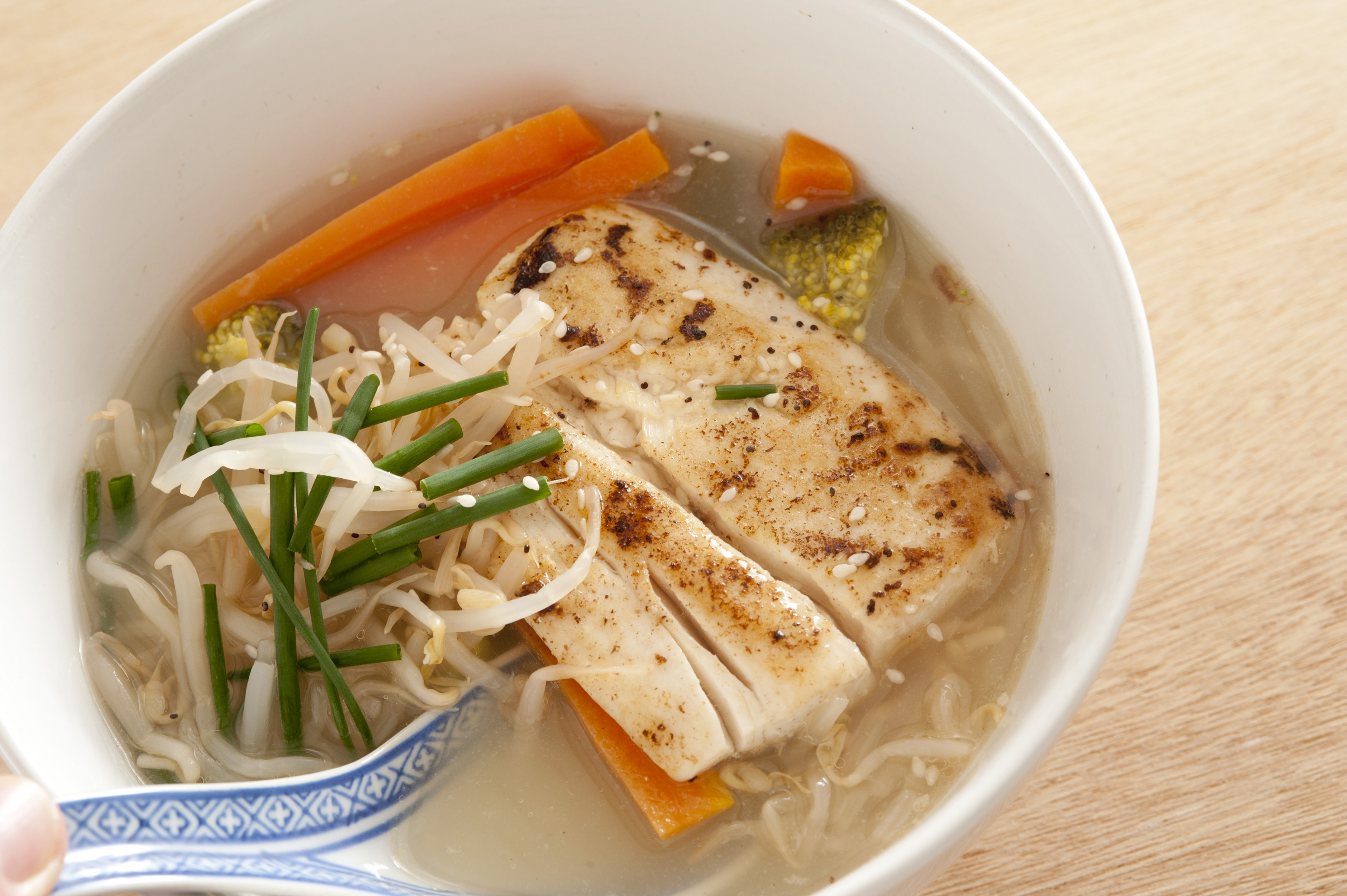 Spoon being placed in delicious Asian cuisine meal of soup broth with milkfish chunks, seasoning, chives, carrots and noodles