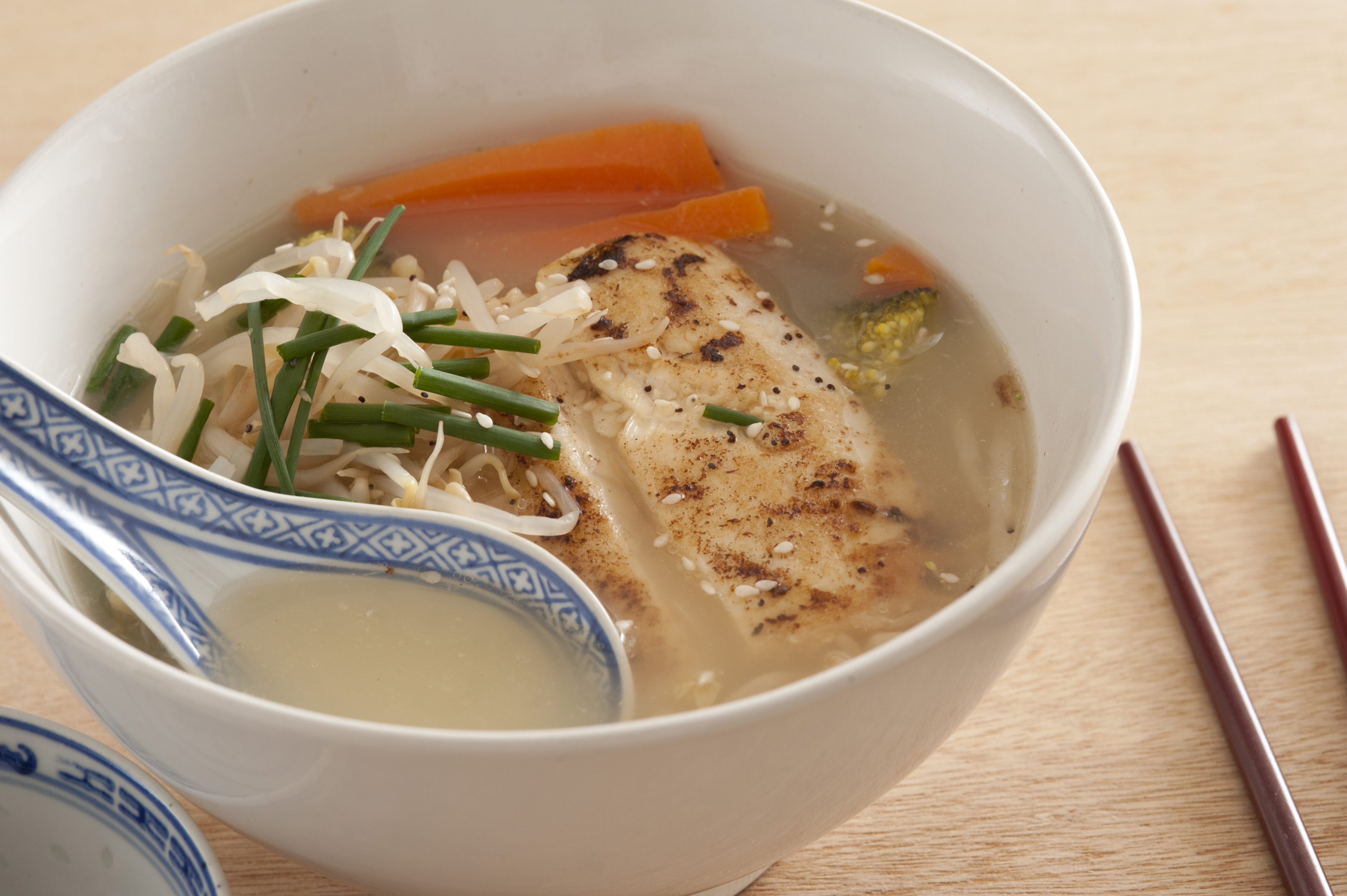 Asian soup made of grilled meat in clear broth, carrot sticks, chives, sliced onions and with a decorative ceramic spoon