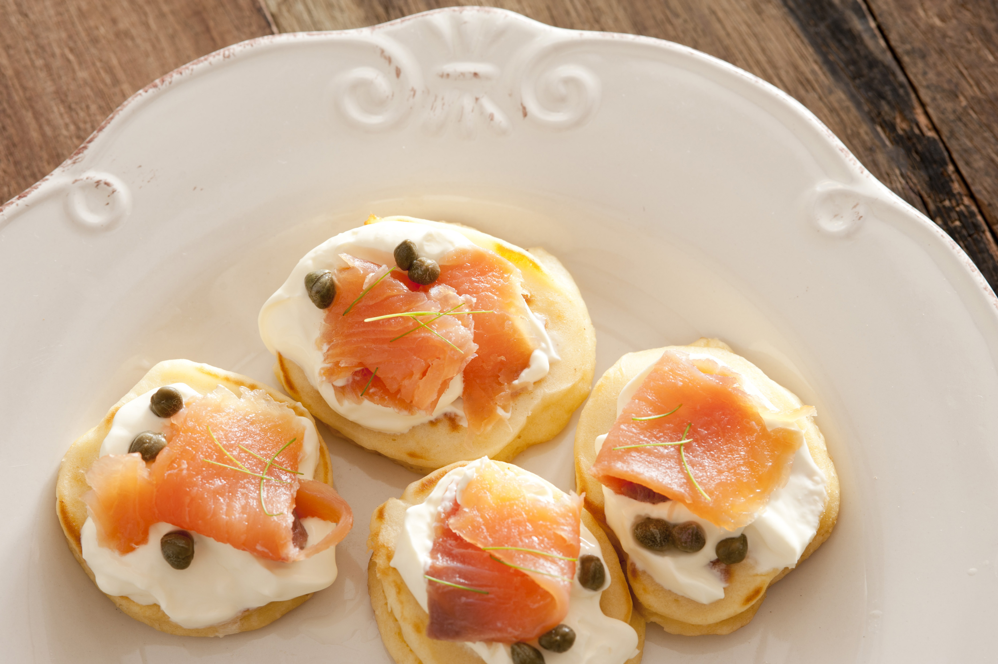 Capers and raw fish blini appetizers on white porcelain decorative plate over wooden table