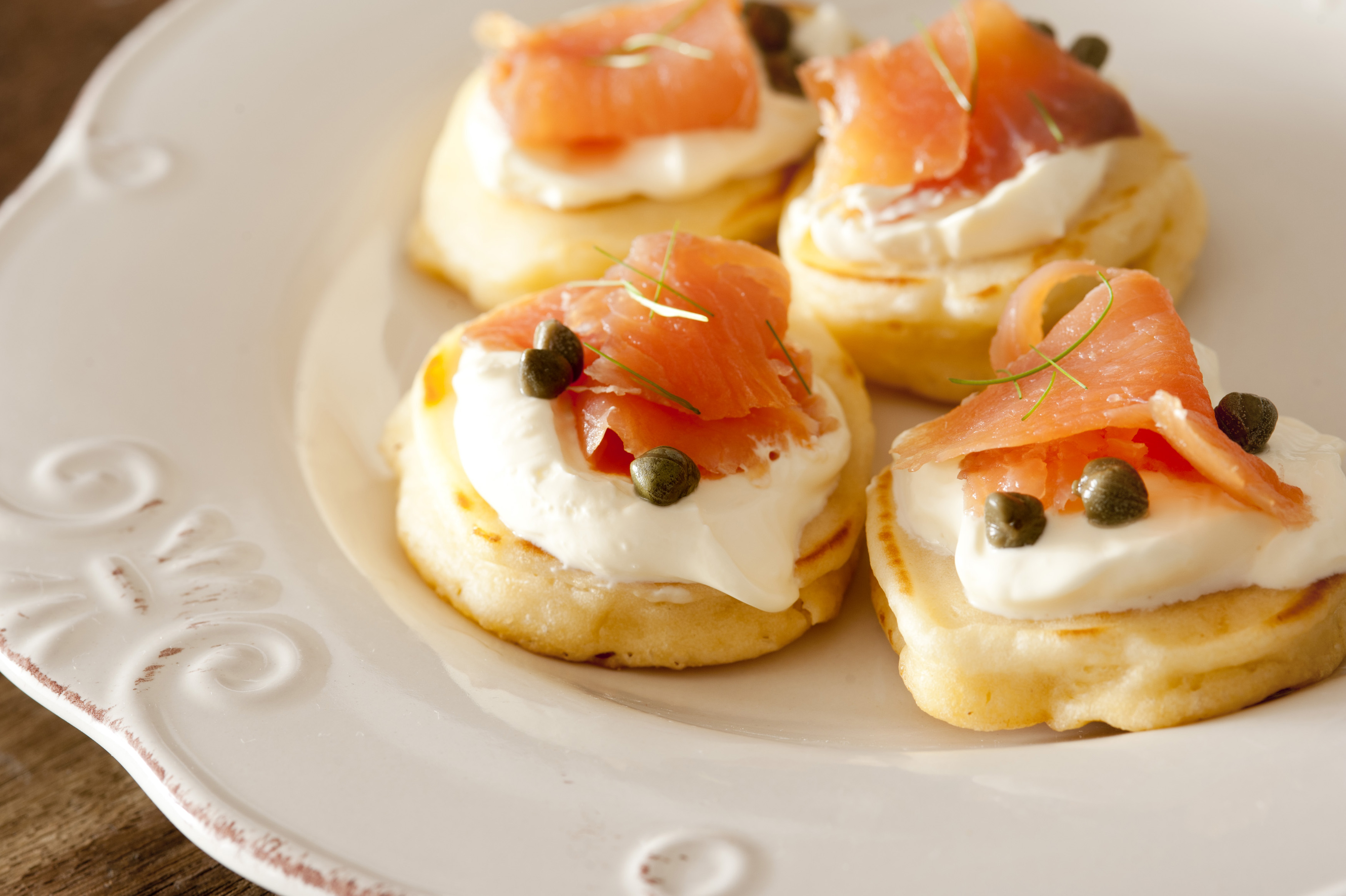 Four raw fish and cheese blini snacks with capers and herbs on white glossy ceramic plate