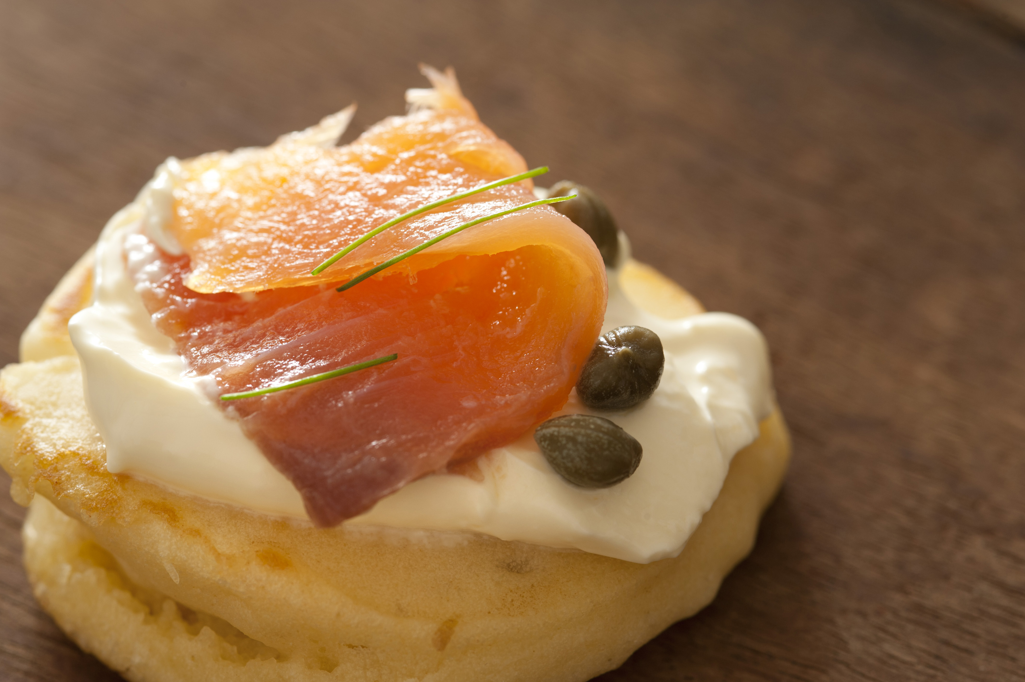 Gourmet appetizer with smoked salmon, capers and cream cheese served on a blini on a wooden table