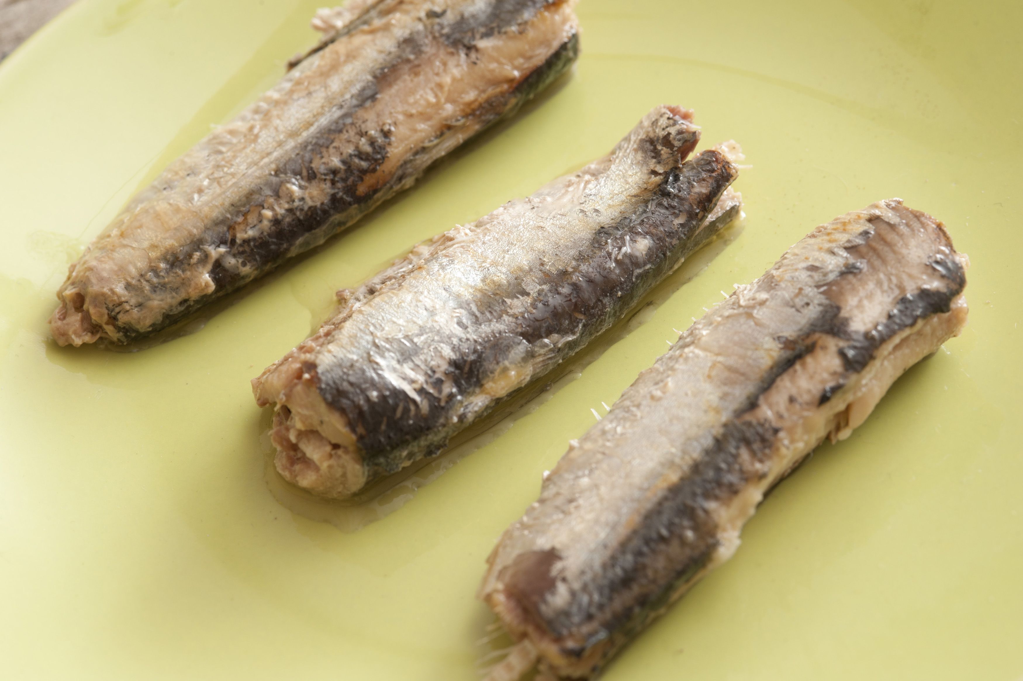 Three canned sardines on a yellow plate arranged separately in a neat row, close up high angle view