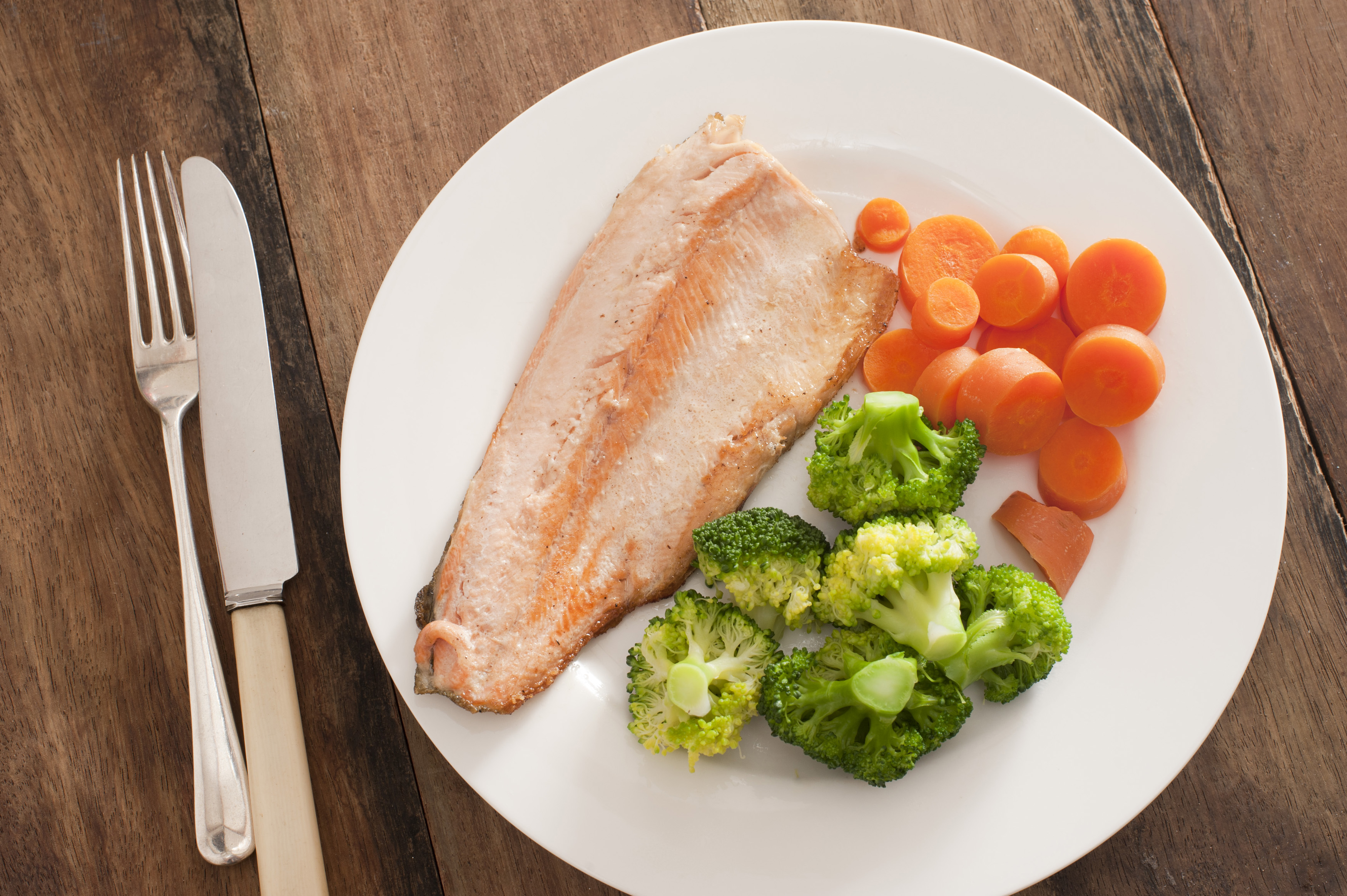 Top down first person view over lean cooked rainbow trout protein with cut broccoli florets and carrot slices in round plate on table