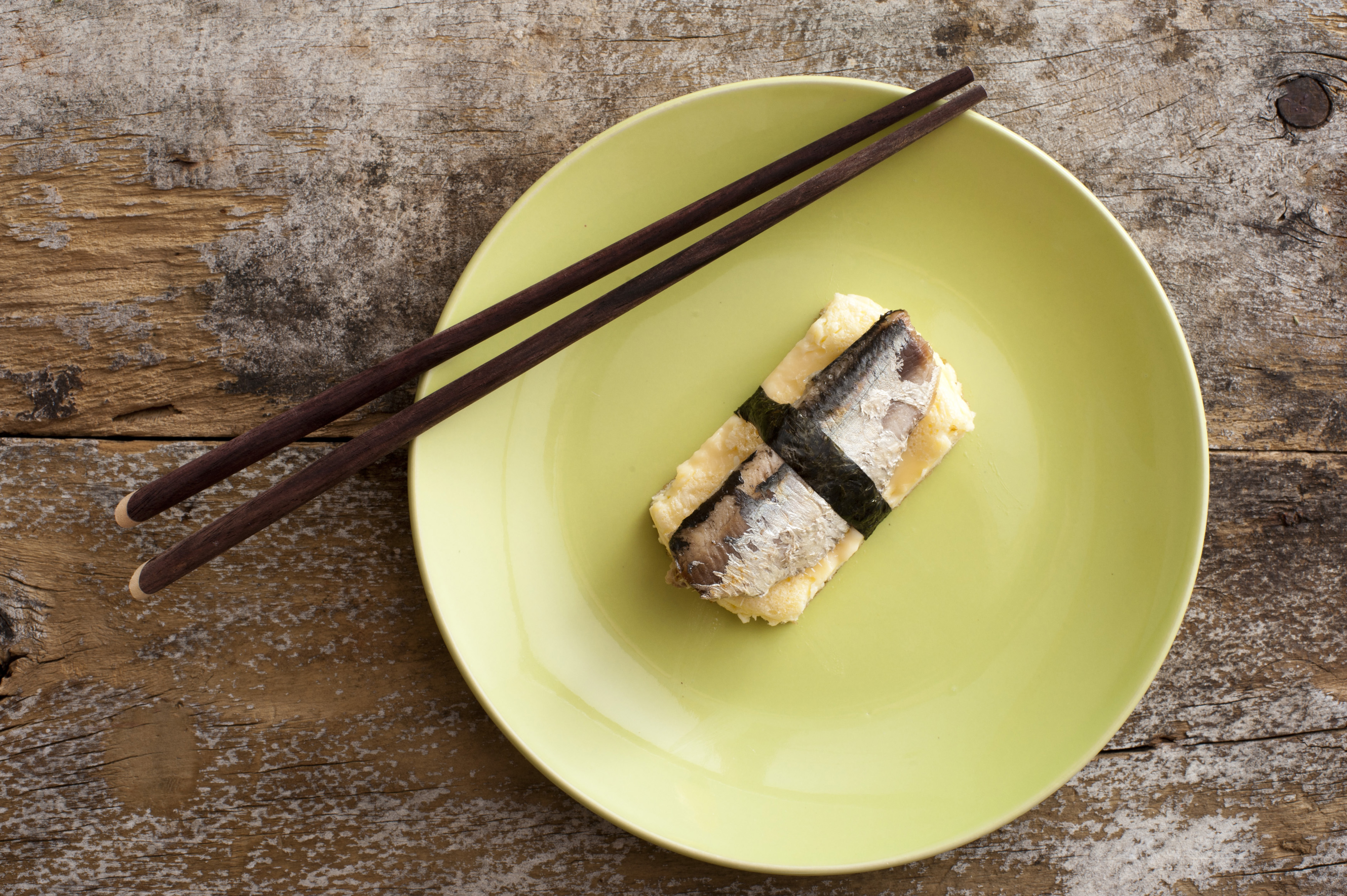 Top down view of fish and egg omelet square in plate with chopsticks over weathered wooden table