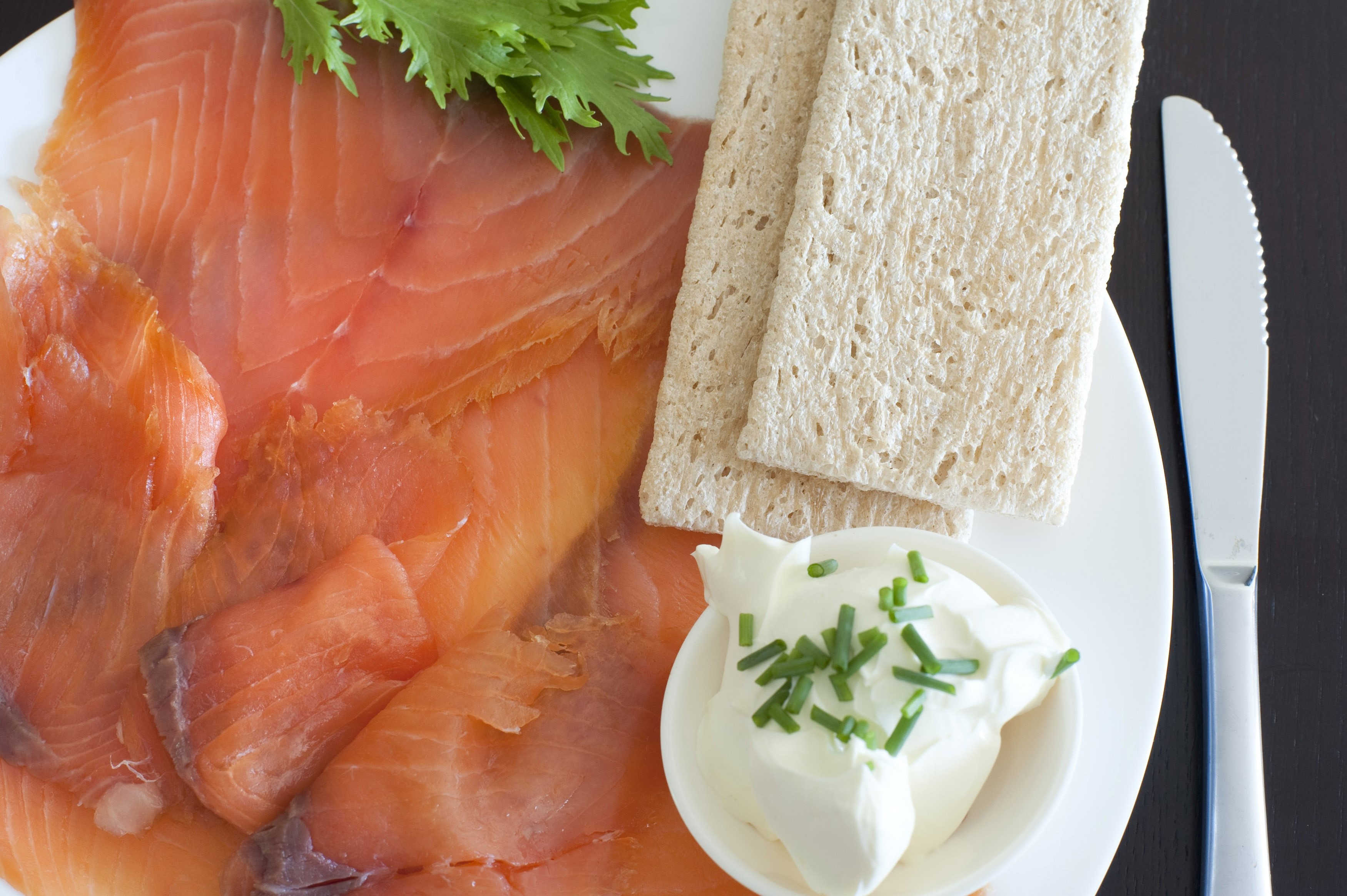 Gravalax, or thinly sliced cured and smoked salmon, with cream cheese and crispbread, close up overhead view