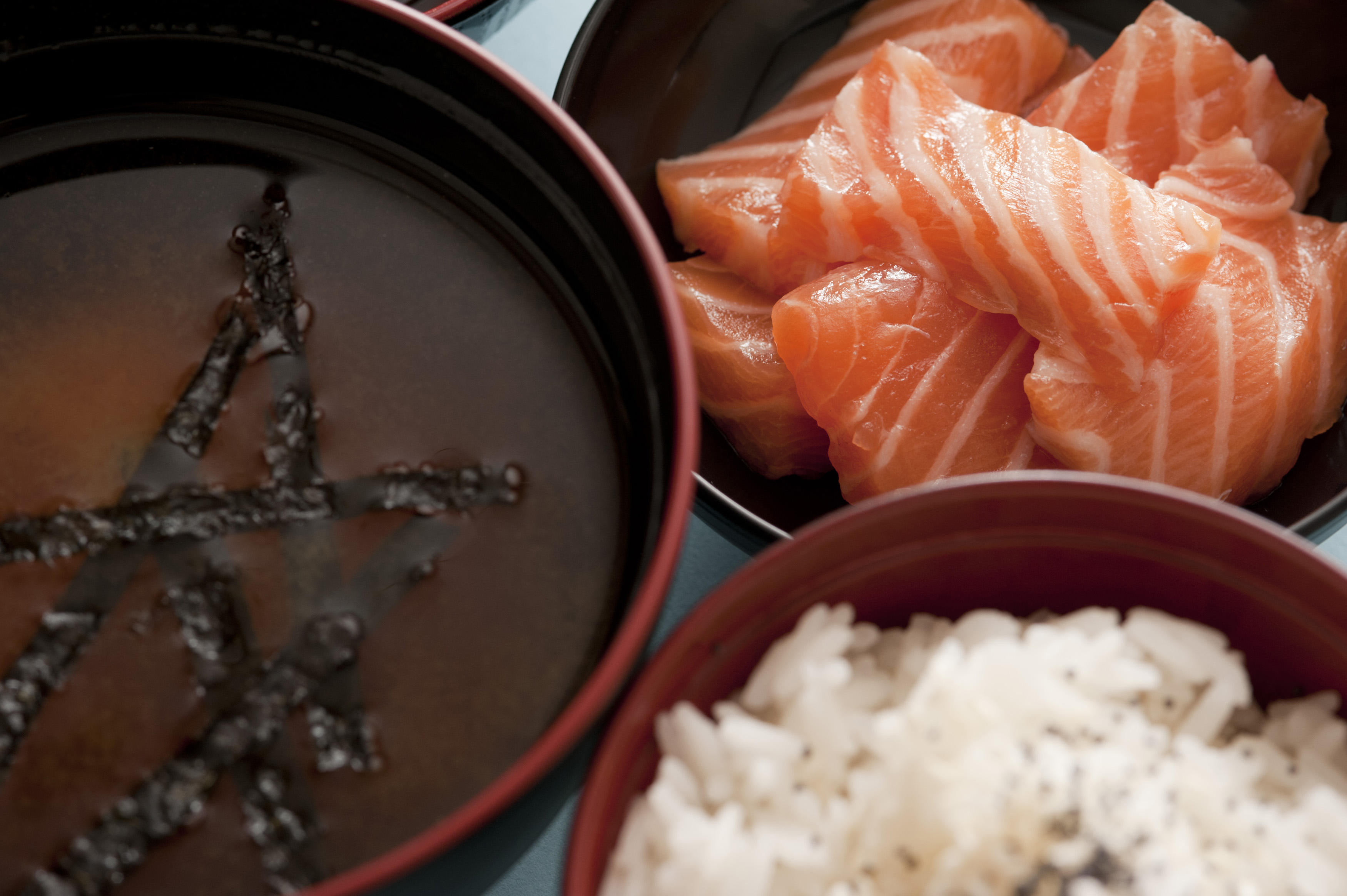 Bowls of freshly prepared Japenese cuisine consisting of bowls of delicious miso soup, raw salmon and white rice close up
