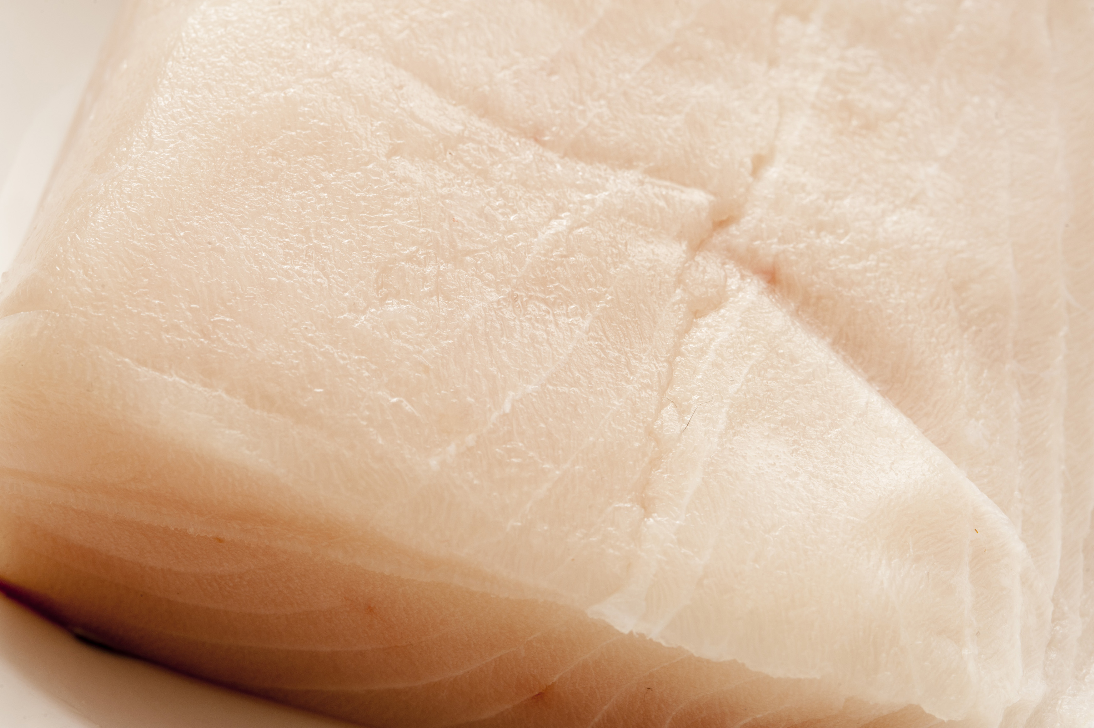 Cropped close up view on cut of raw mackerel fish meat with lines and slightly dry surface
