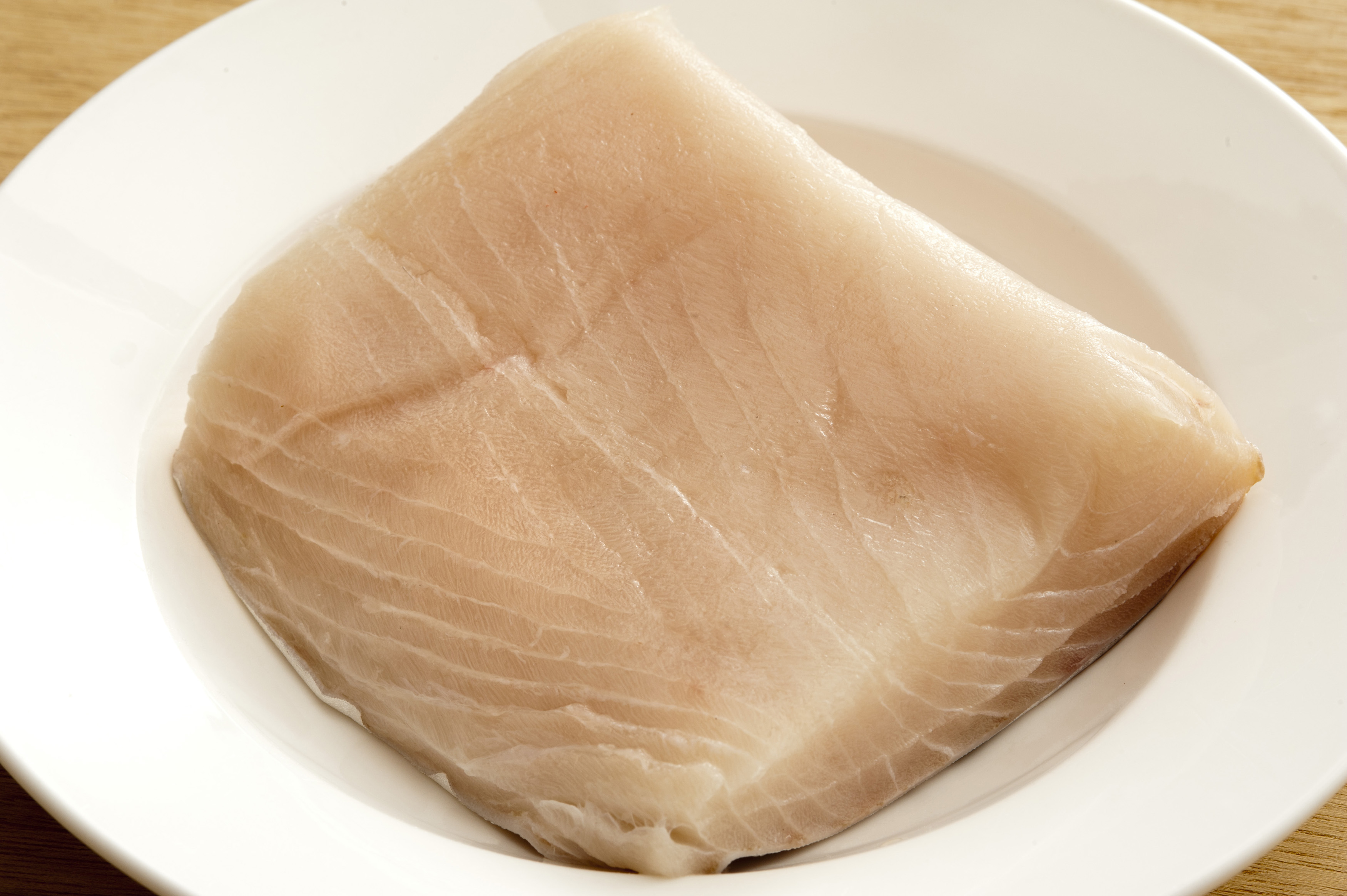 Top down close up view on single square shaped piece of raw mackerel meat in the middle of round white china plate