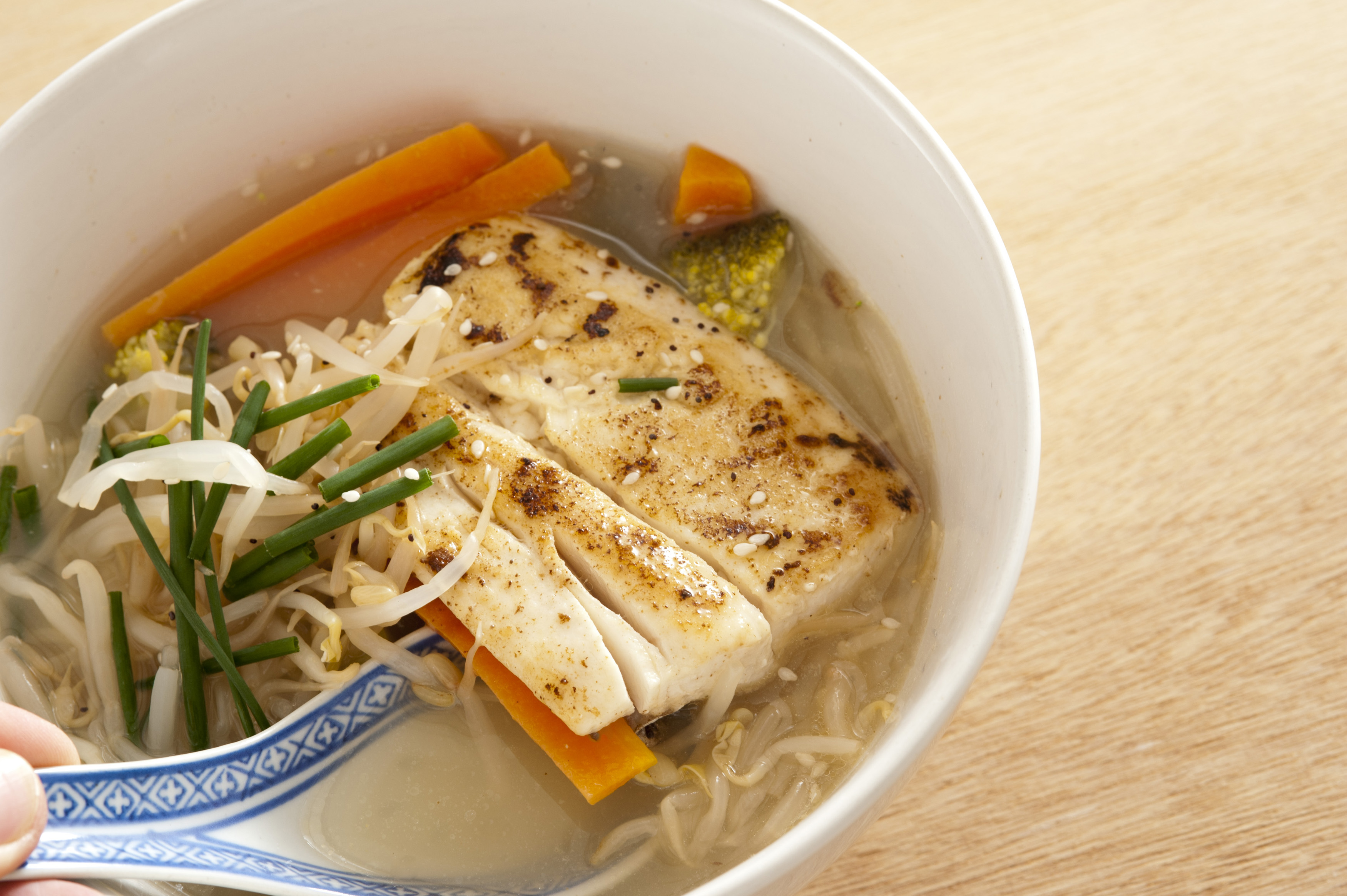 Hand holding a decorative blue and white spoon in milkfish soup bowl with noodles, chives and carrots in the broth