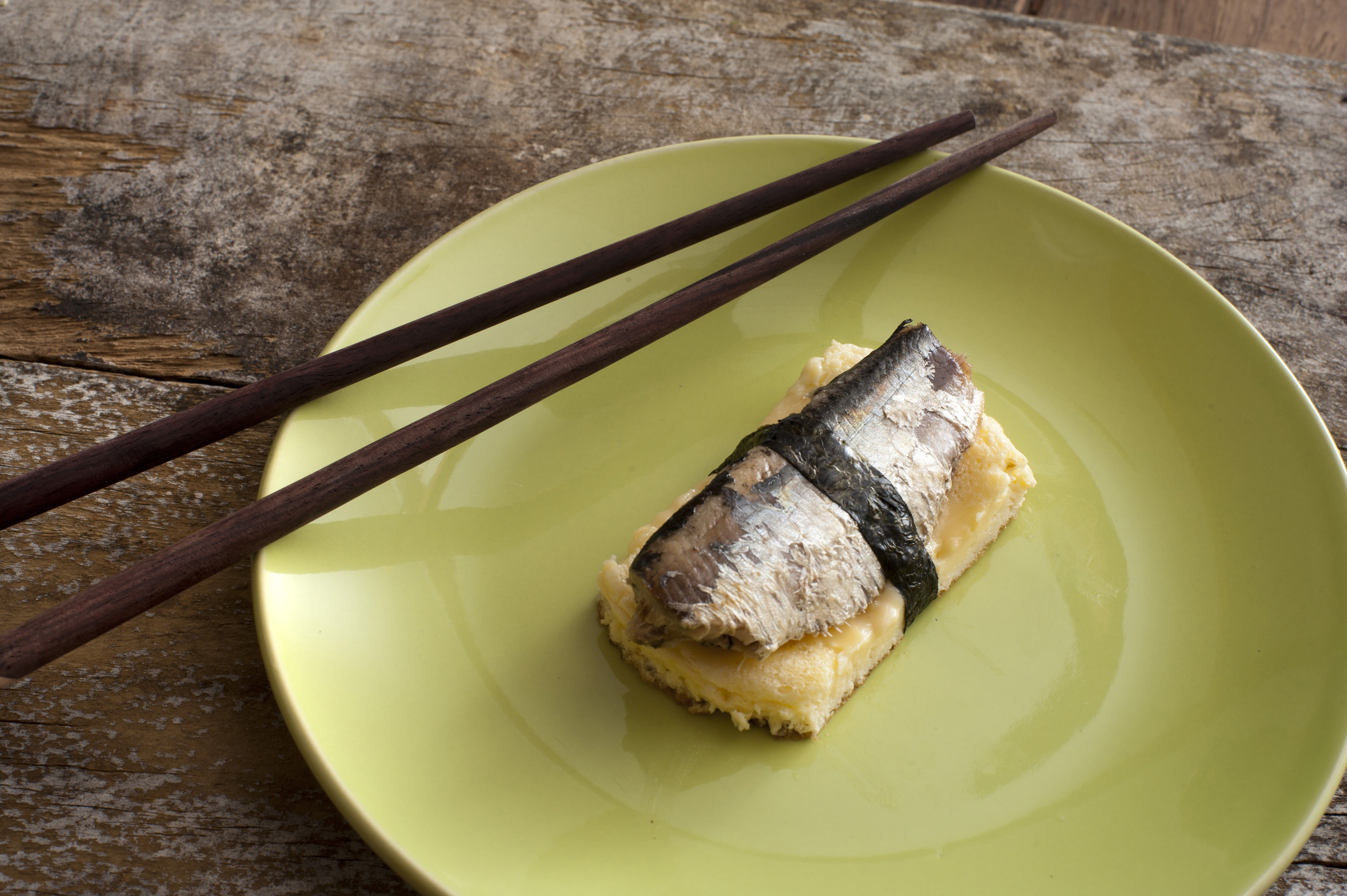 Pair of dark brown chopsticks on round green plate of omelete or tamagoyaki and fish bound together with seaweed over rustic wooden table