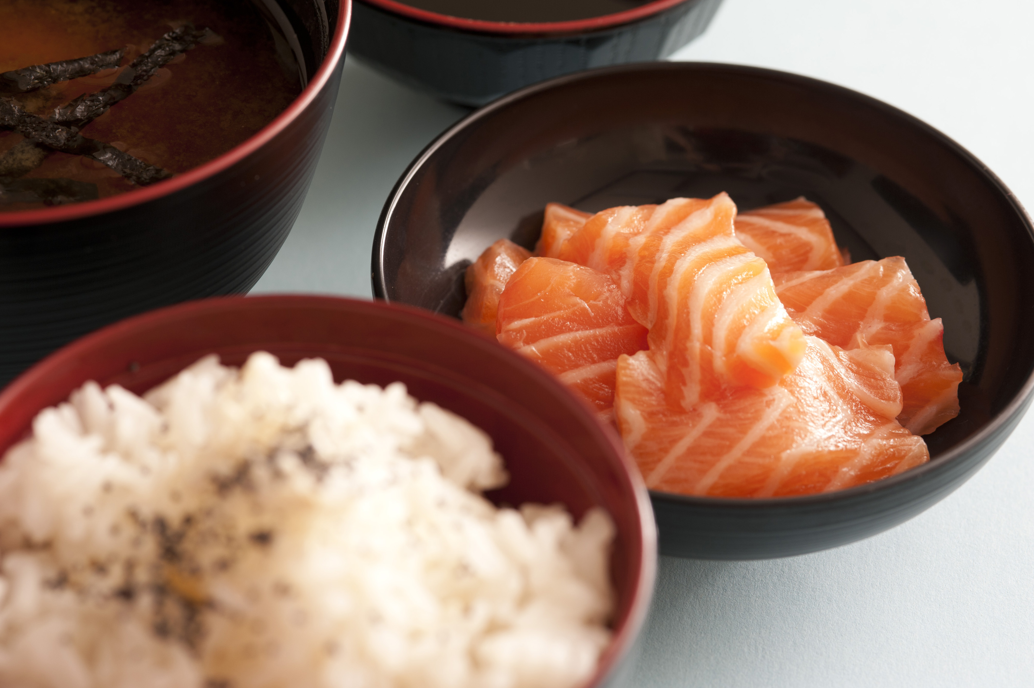 Selective focus view on round bowl of raw red salmon chunks next to seasoned white rice and other dishes