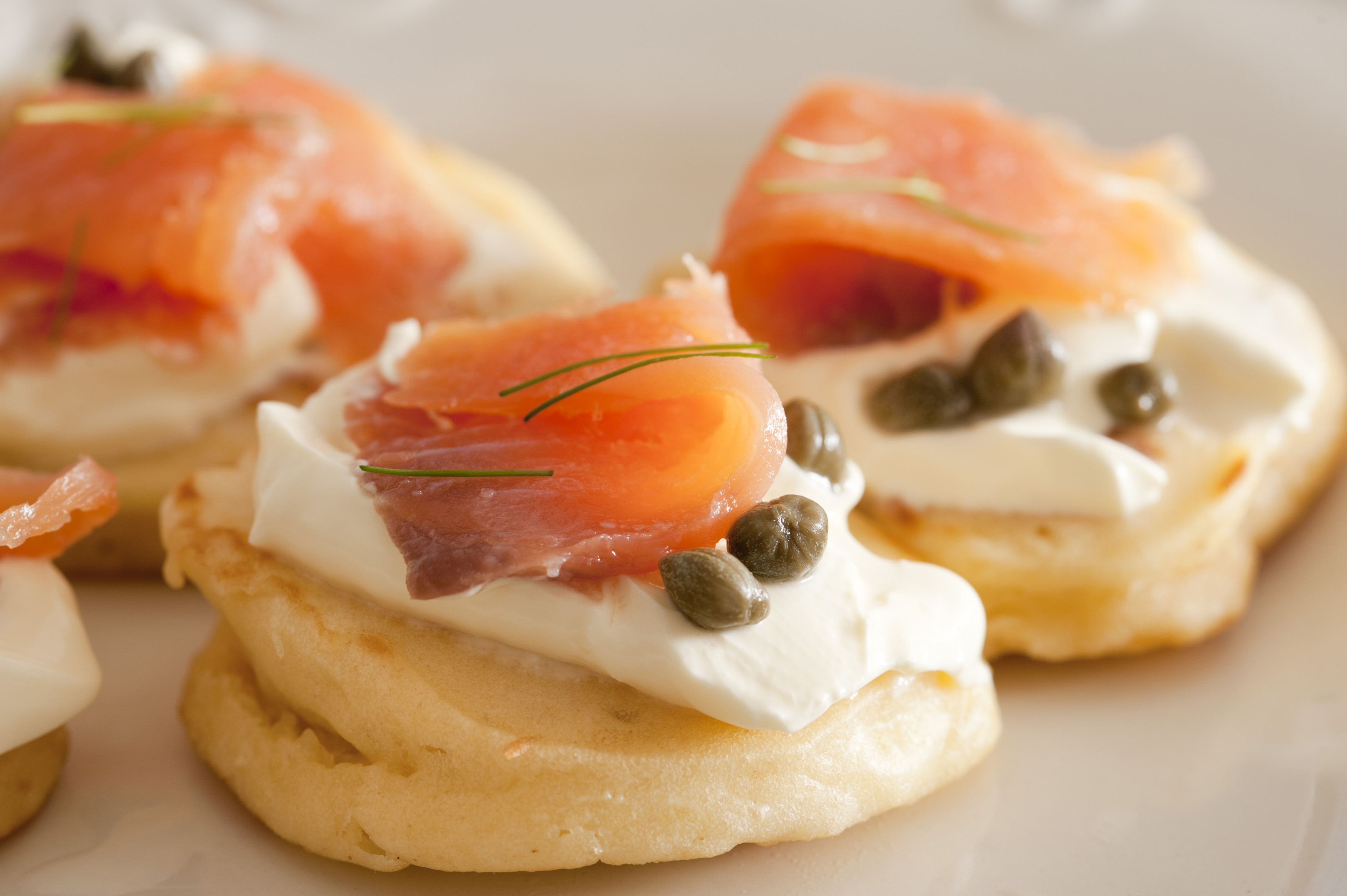 Close up view on delicious capers and raw fish blini appetizers showing smooth texture and little herb topping