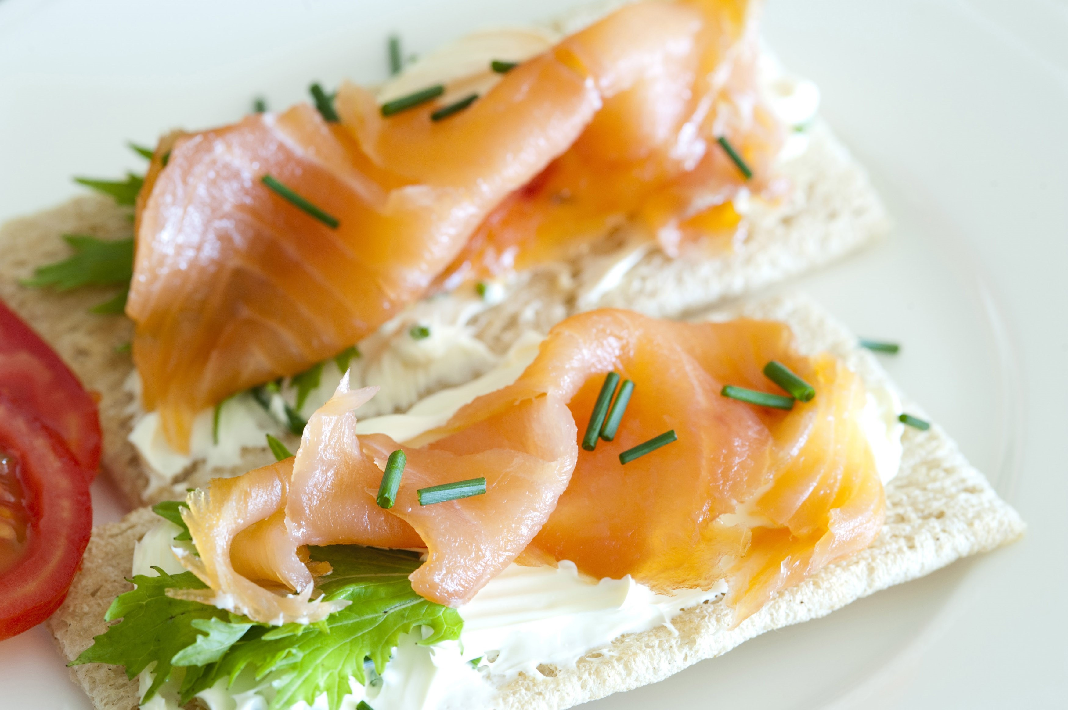Gourmet lunchtime snack of thinly sliced cured and smoked marine salmon on crispbread with fresh lettuce and chives