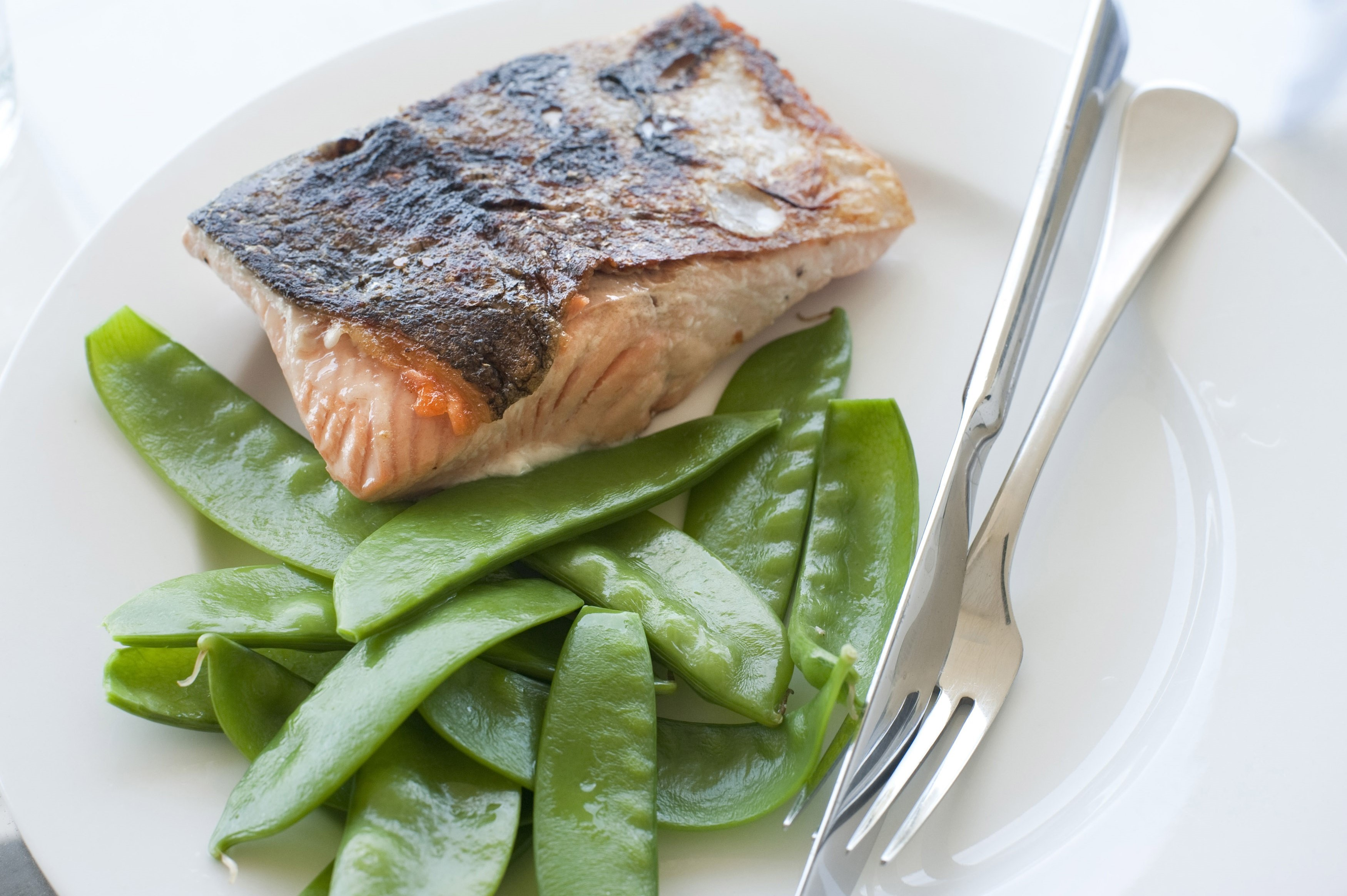 Cooked salmon fillet steak with sugarsnap peas served on a plain white plate with silver cutlery