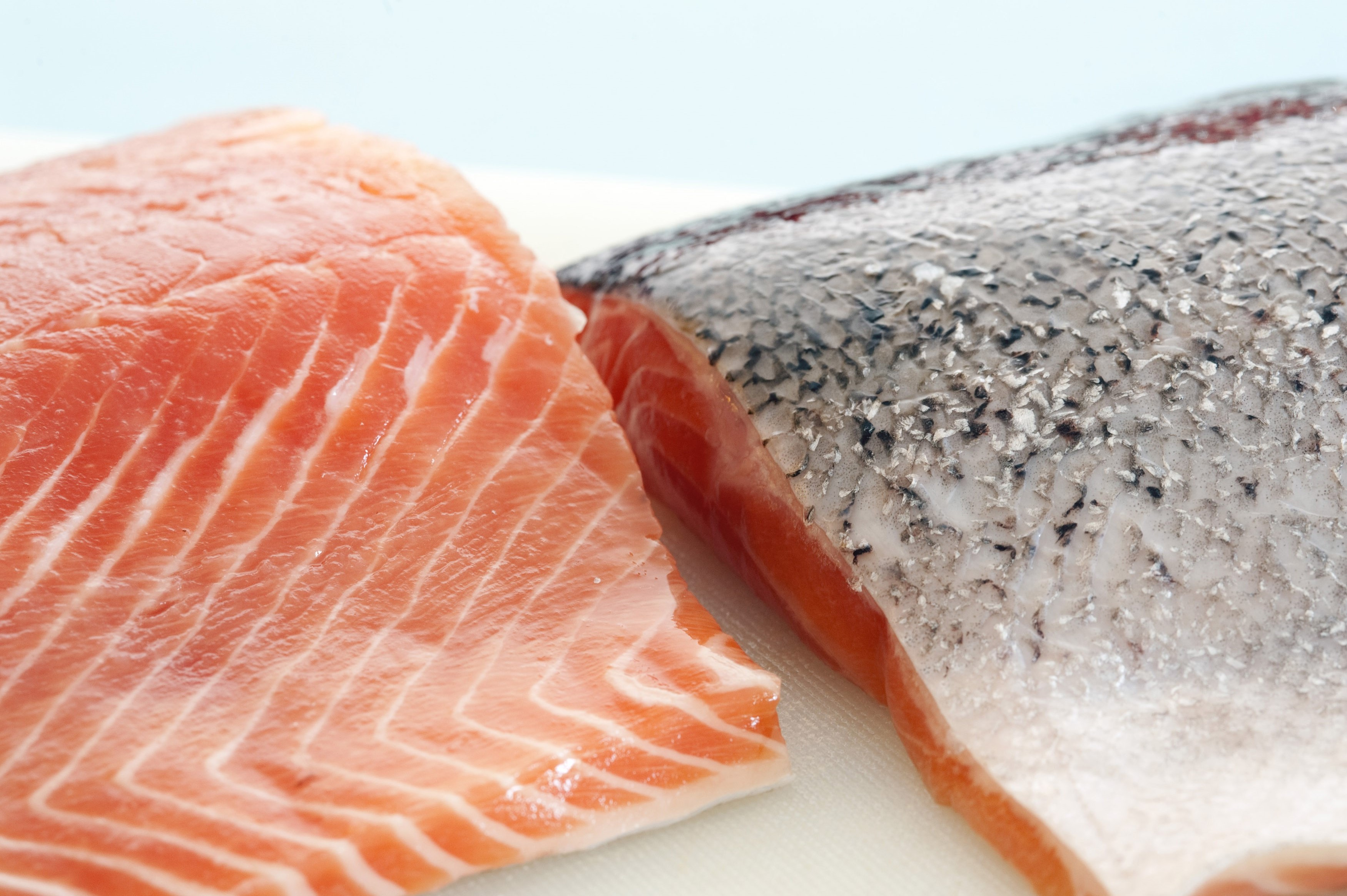 Two fresh raw salmon fillets, one with the flesh exposed and one showing the skin texture while preparing a gourmet seafood meal