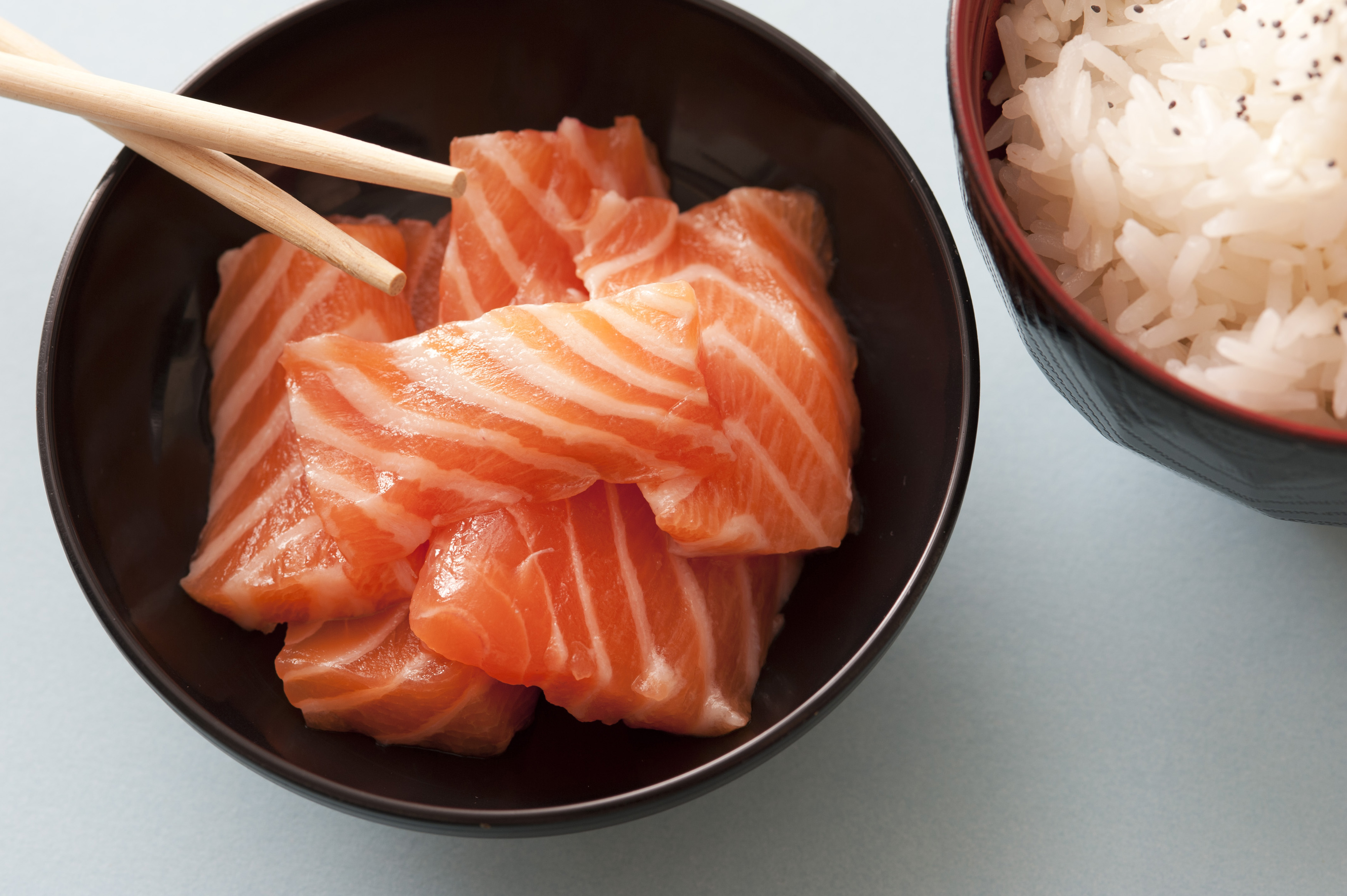 Close up view on raw pink salmon pices in little bowl with wooden chopsticks and herbed white rice