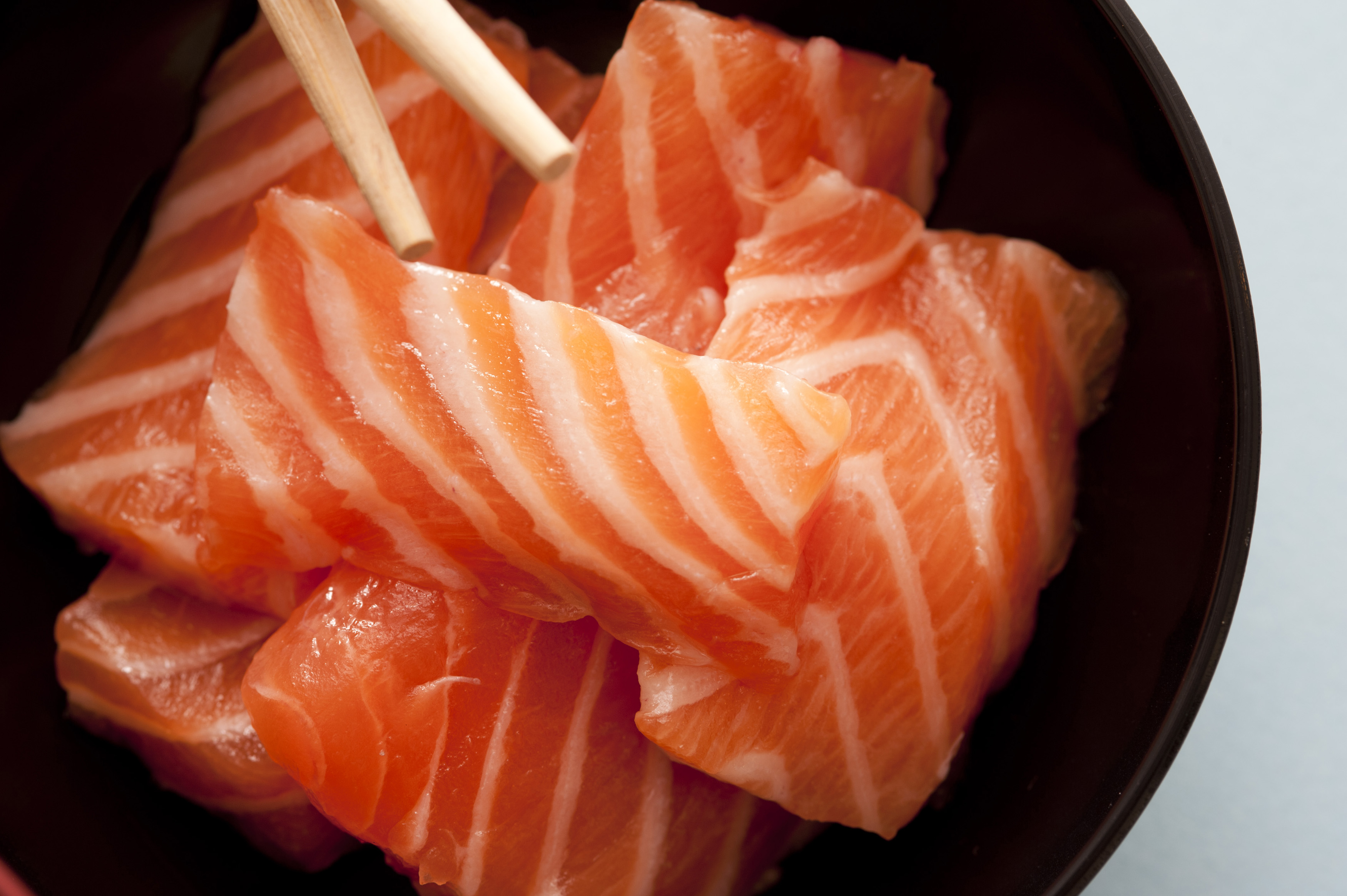 First person perspective view from top down over sashimi raw fish strips with chopsticks close up
