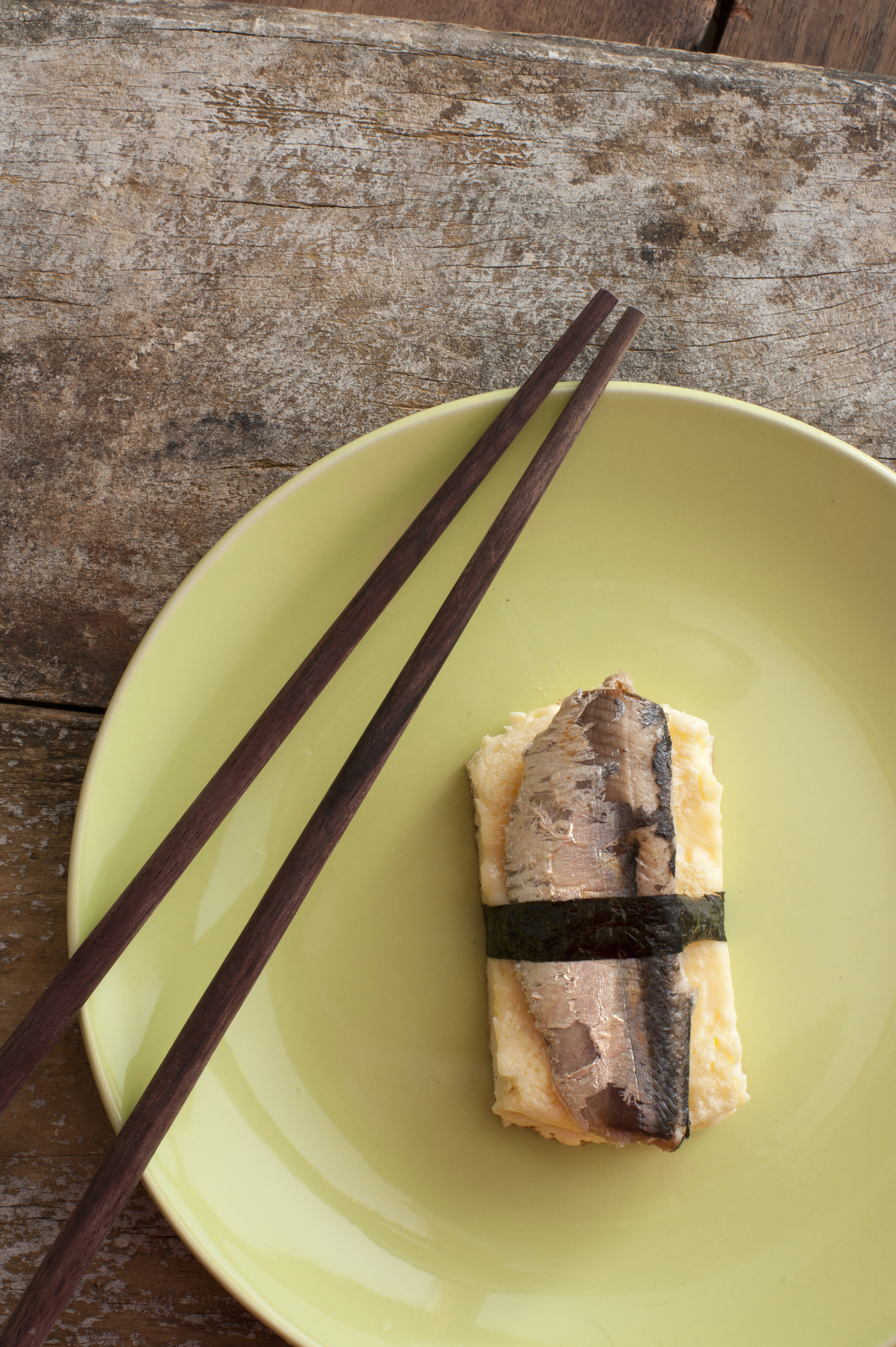 Top down view of single serving of wrapped mamagoyaki sardine with brown chopsticks and round green plate