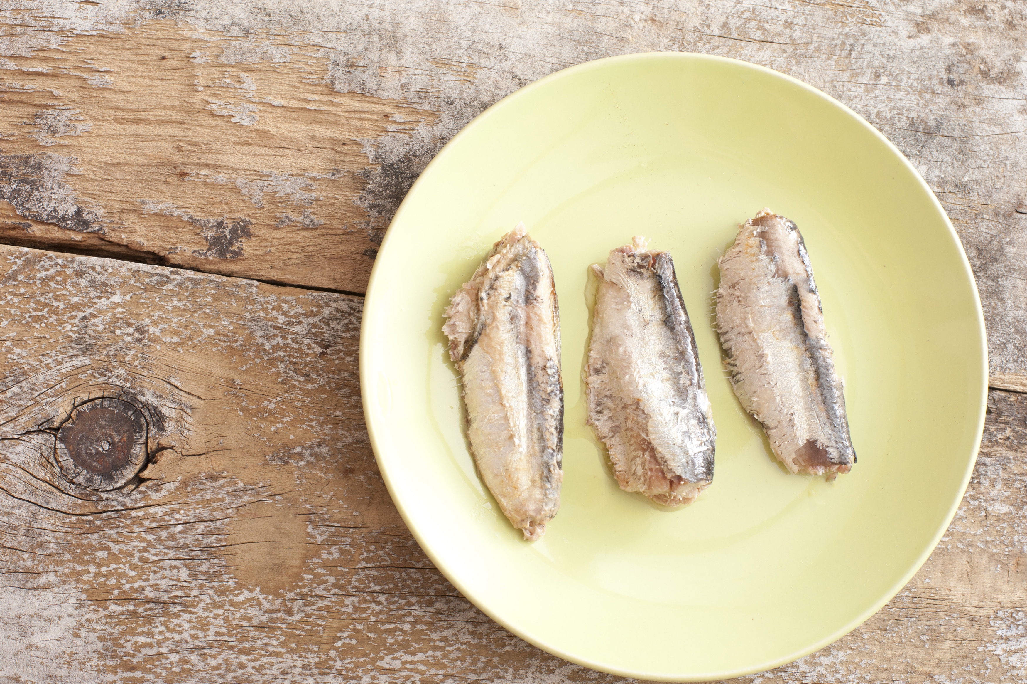 Top down view on three sardines prepared and ready to eat in middle of round plate over old weathered wooden surface