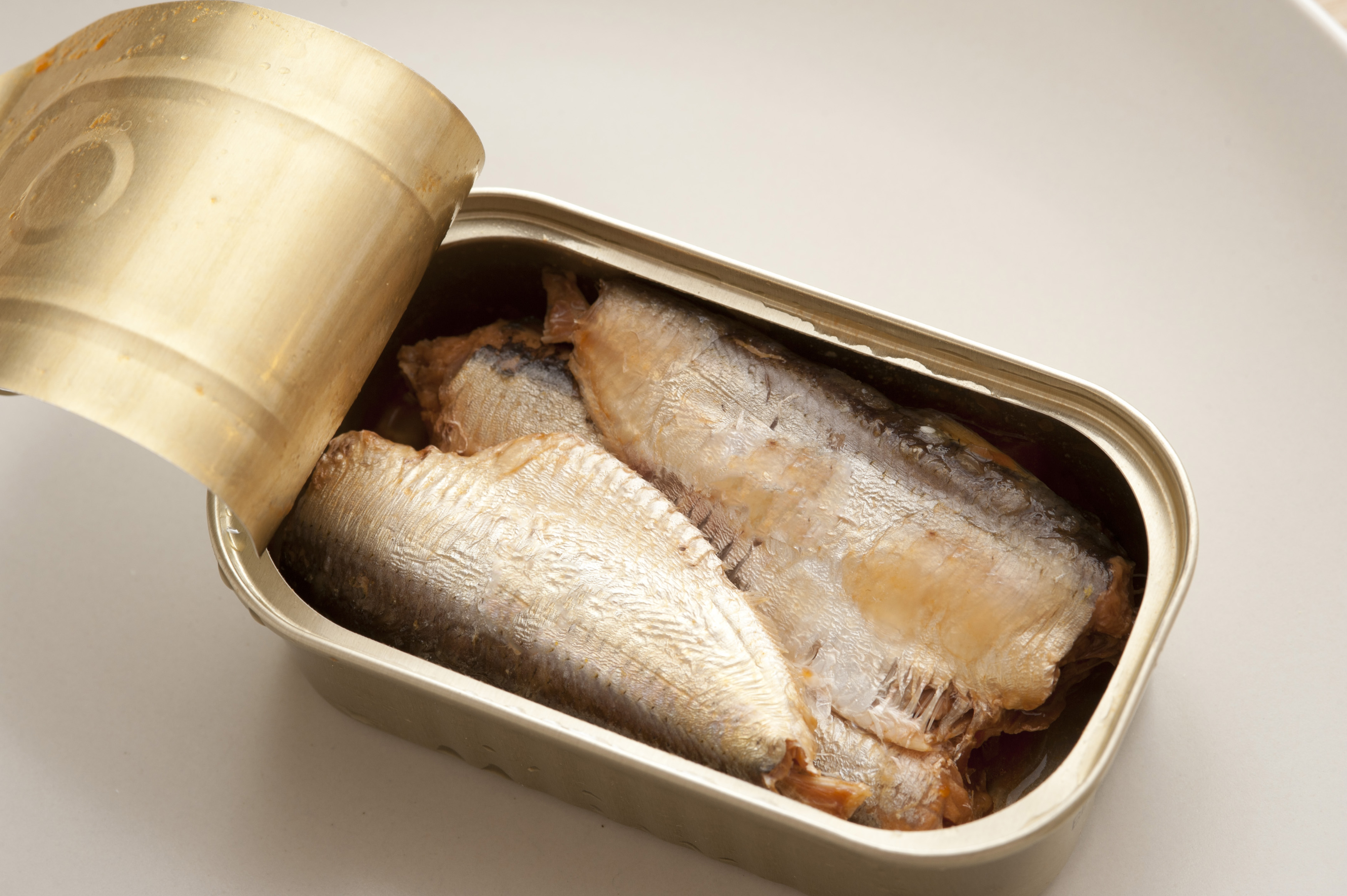 Top down view of sardine fish pieces in rectangular round edged metal can with open lid