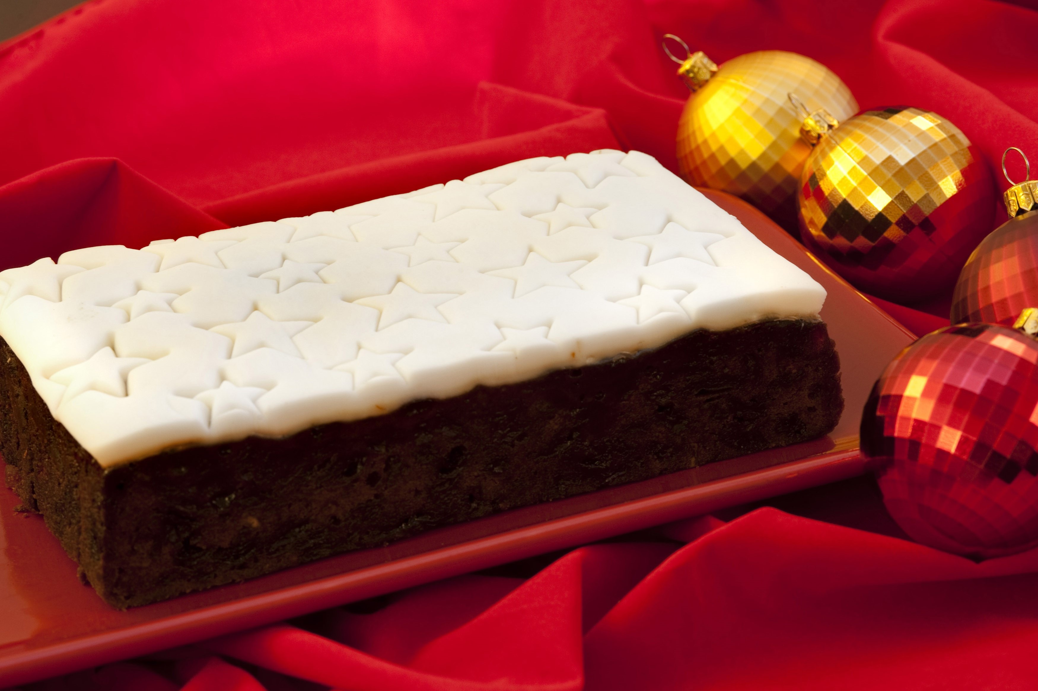 Rich fruity Christmas cake topped with icing decorated with stars on a red cloth with festive Christmas baubles